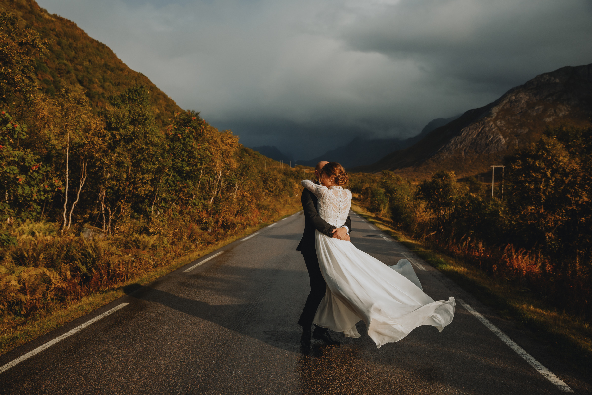 Groom sweeps up bride a remote road in Lofoten Norway- photo by Christin Eide Photography