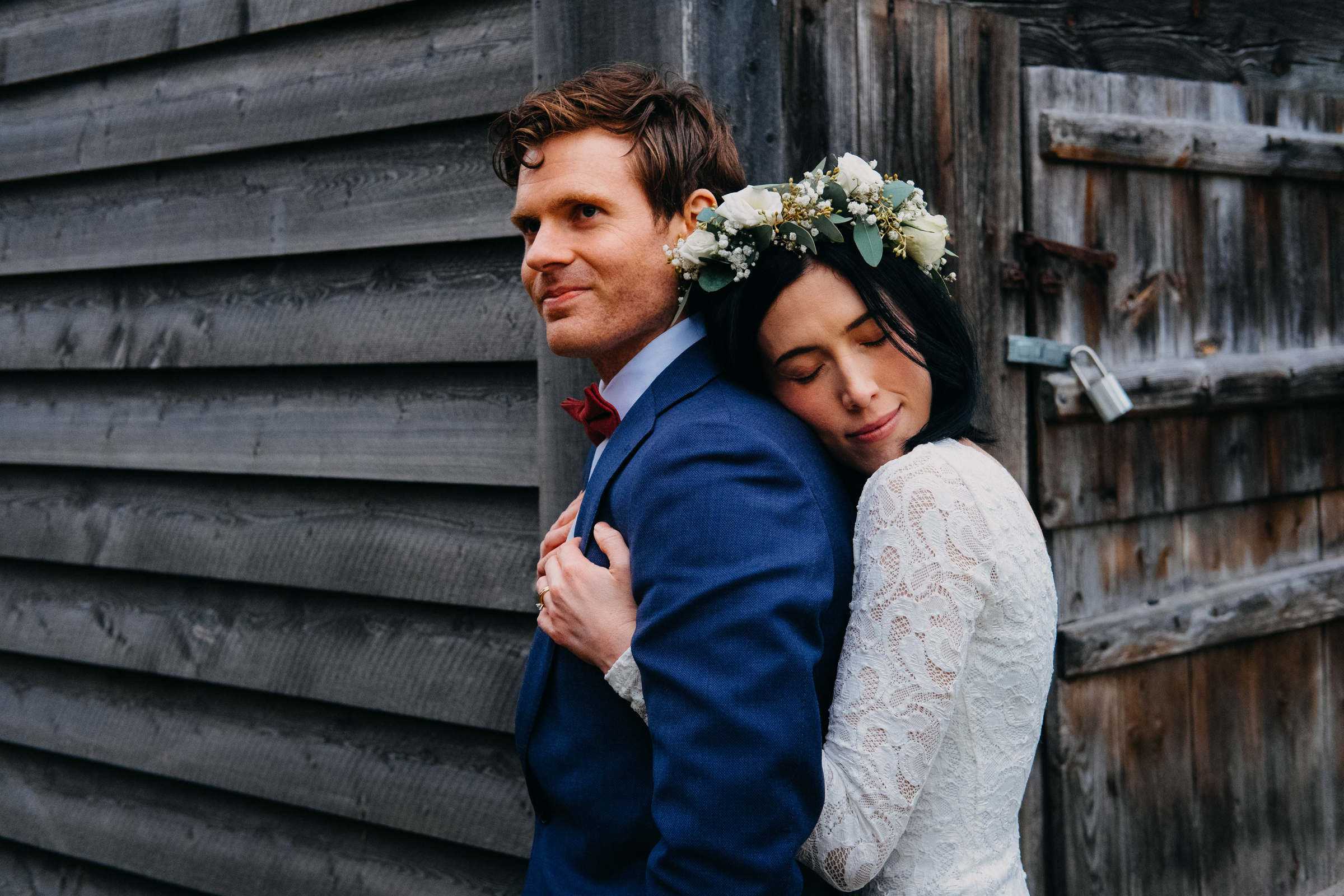 Sweet couple embrace against weathered wood cabin - photo by Christin Eide Photography