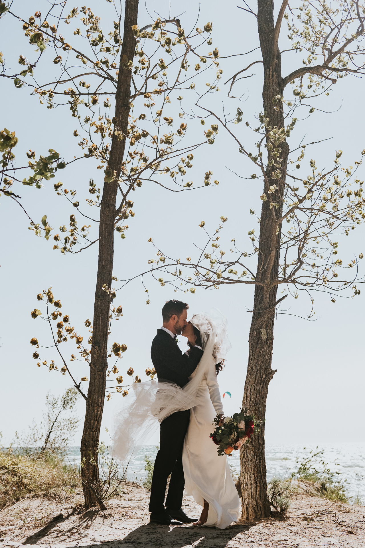 Couple kiss against budding trees at coast - photo by Joel and Justyna