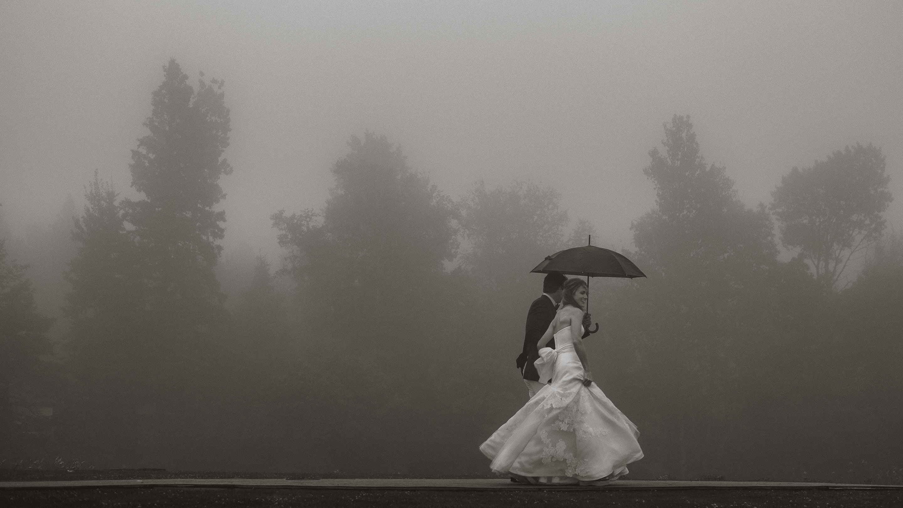 Couple walk with umbrella against misty trees - photo by Joel and Justyna