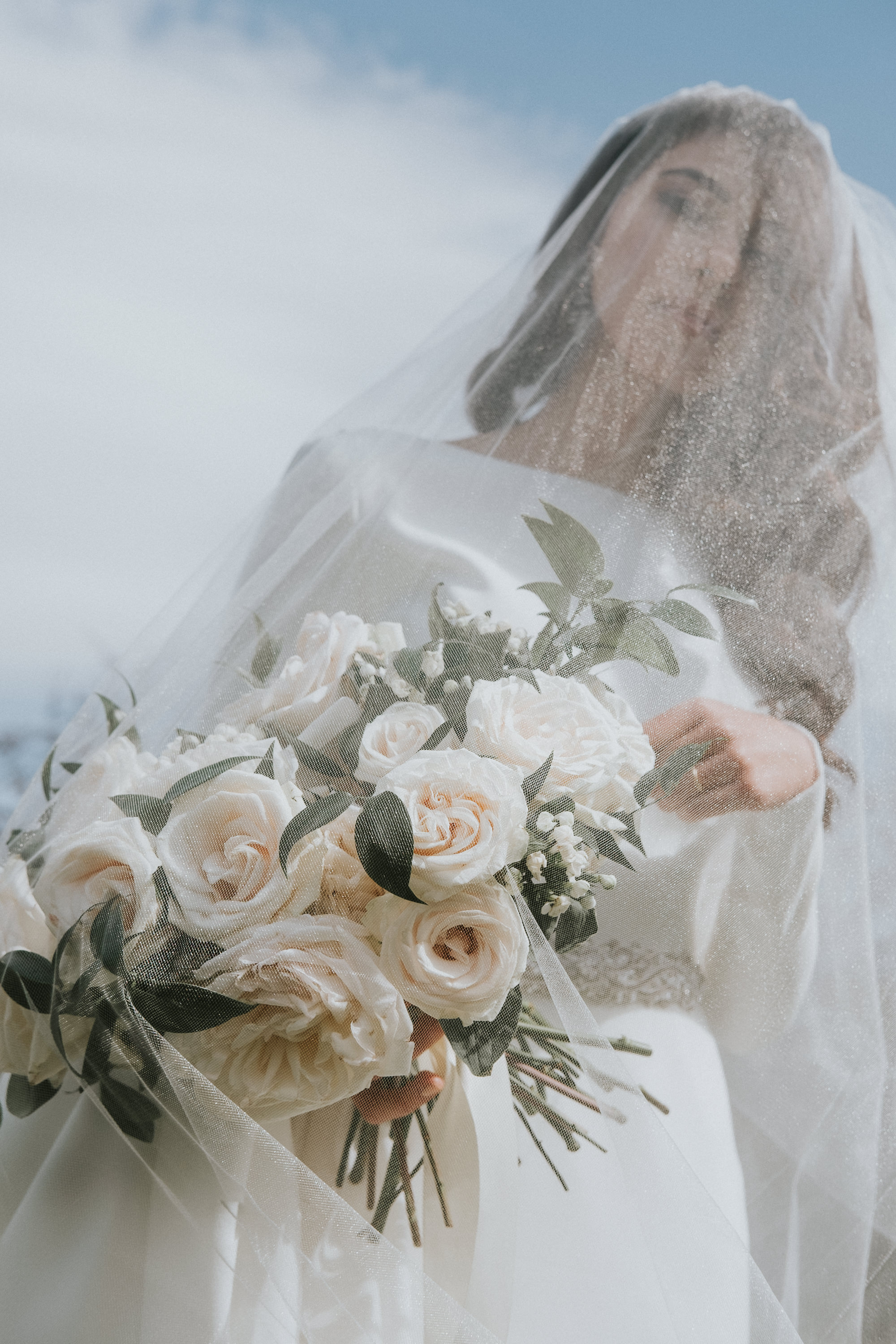 Creative composition of veiled bride with rose bouquet - photo by Joel and Justyna