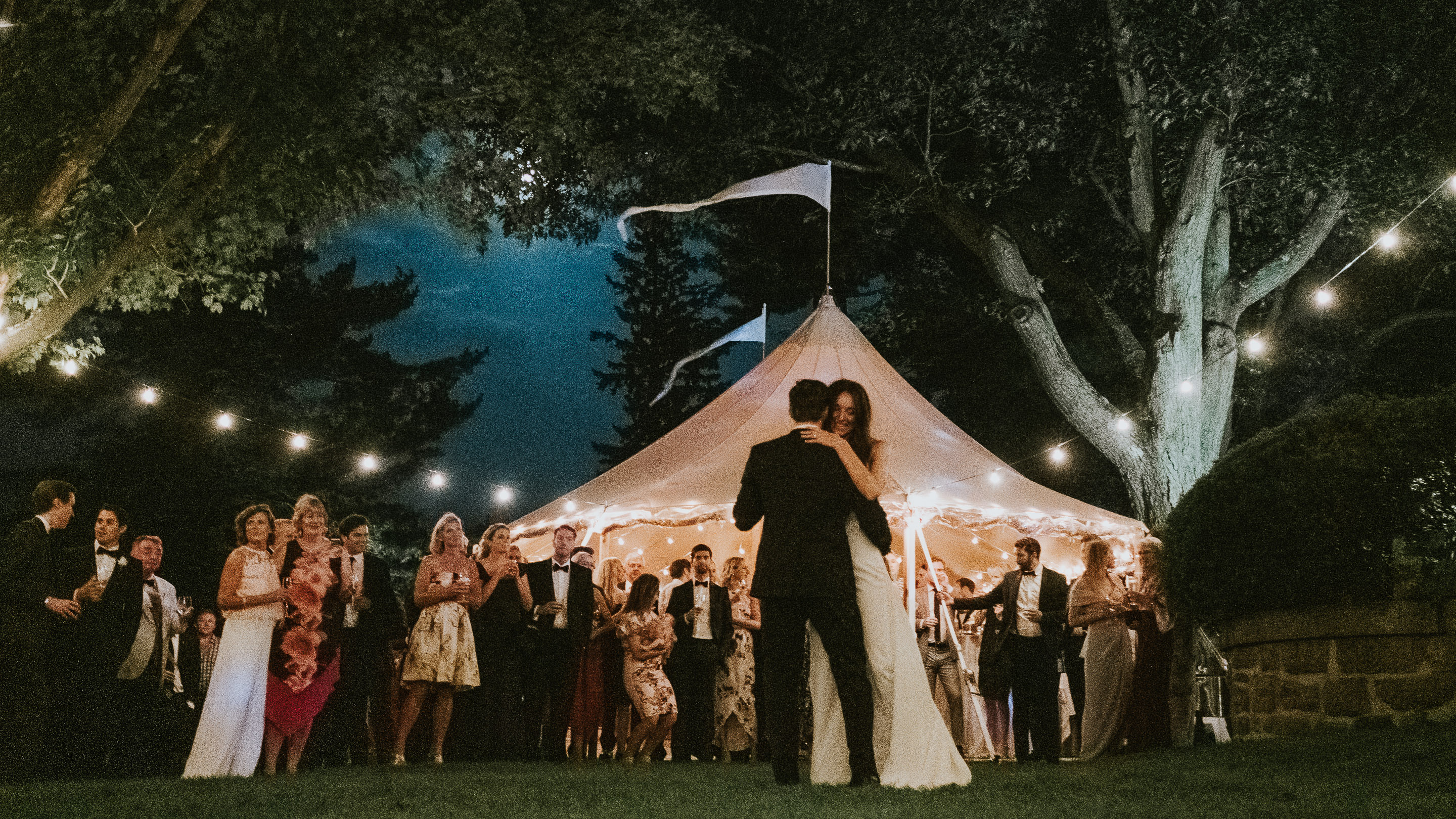 First dance against pink wedding tent - photo by Joel and Justyna