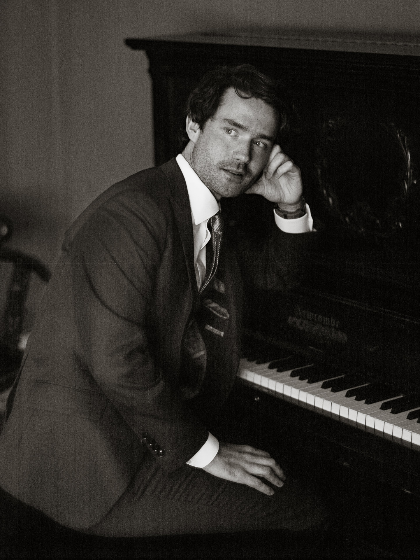 Groom portrait at piano - photo by Joel and Justyna