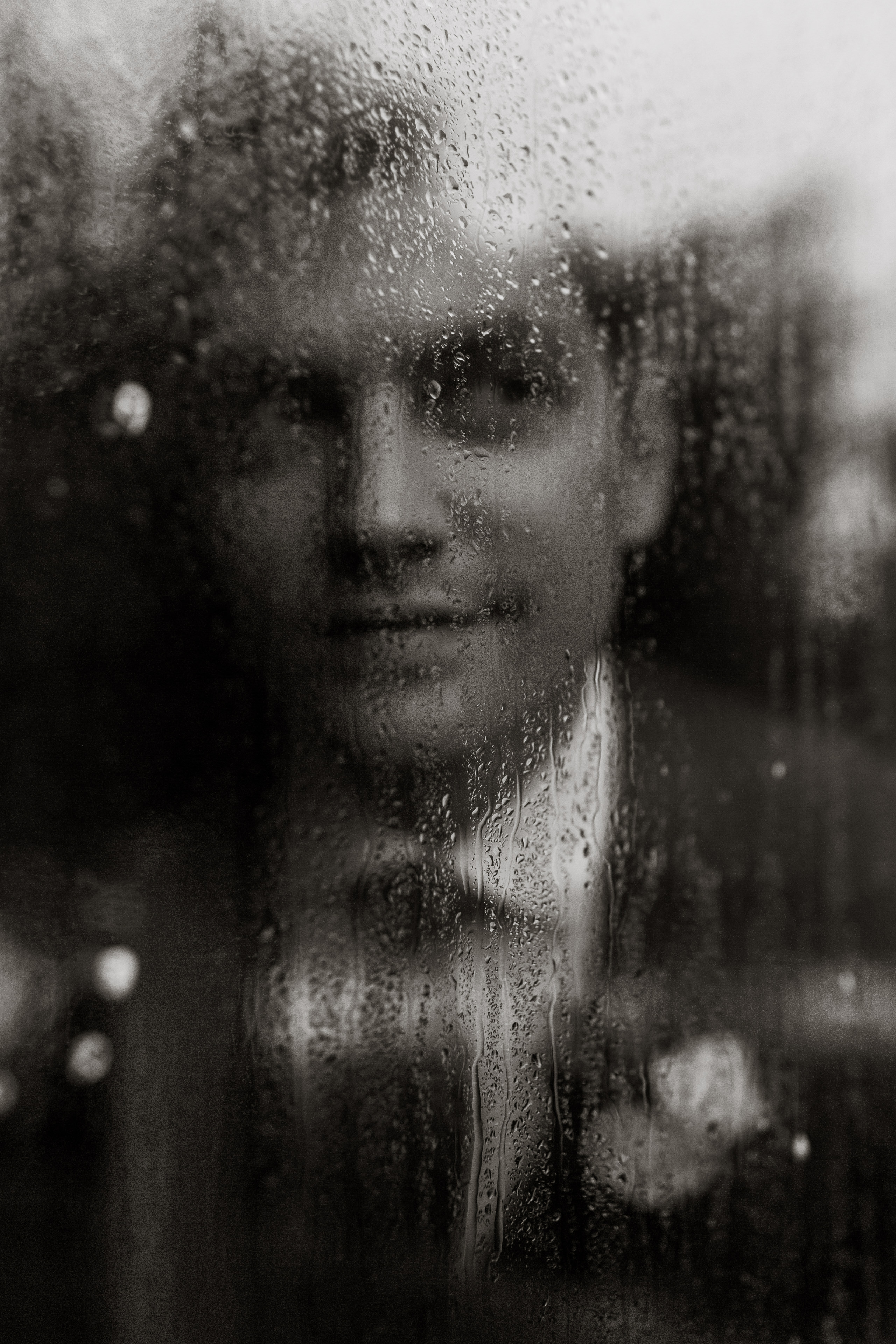Groom seen through rainy windowpane - photo by Joel and Justyna