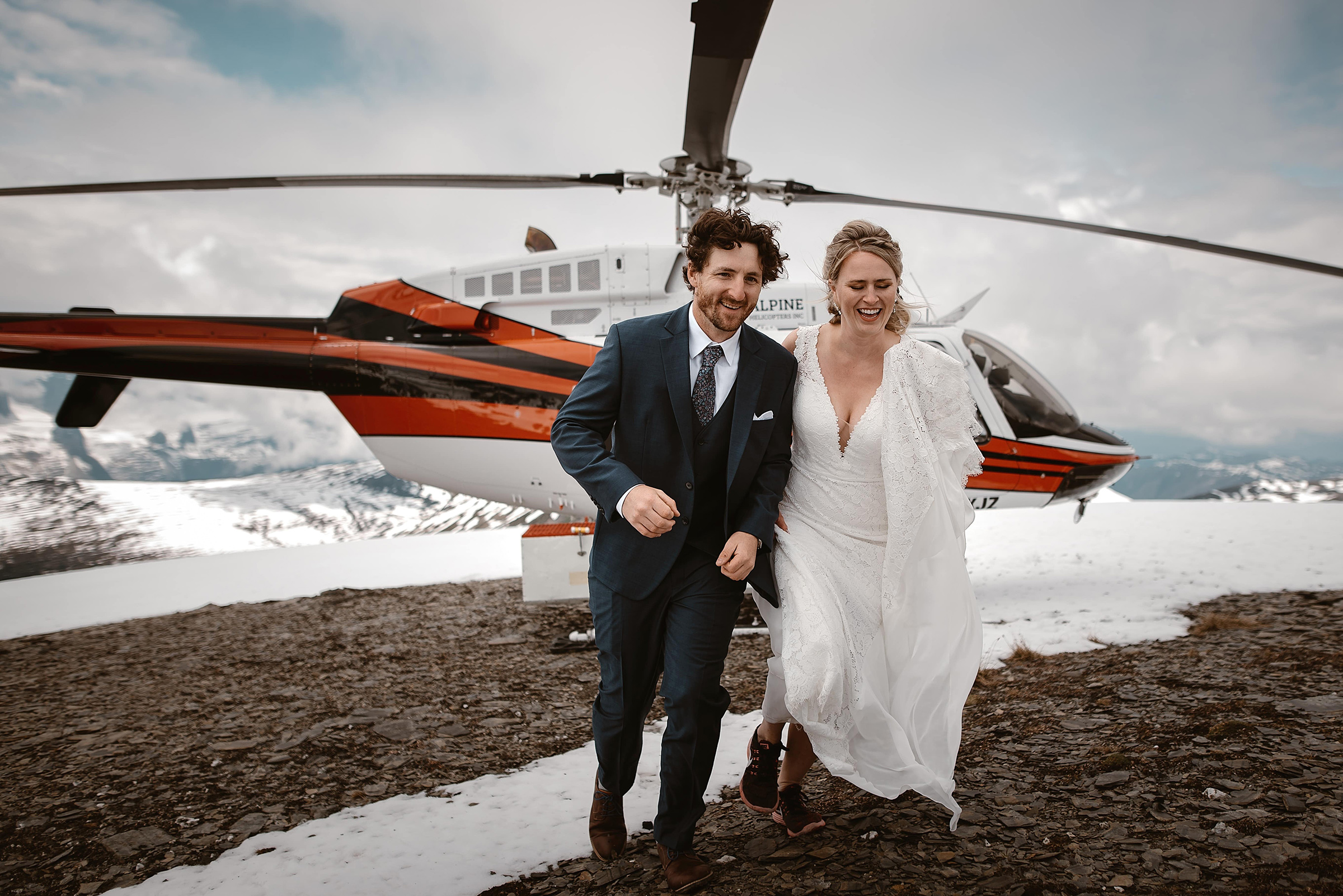 Elopement couple exit helicopter onto snow - photo by Virginia & Evan