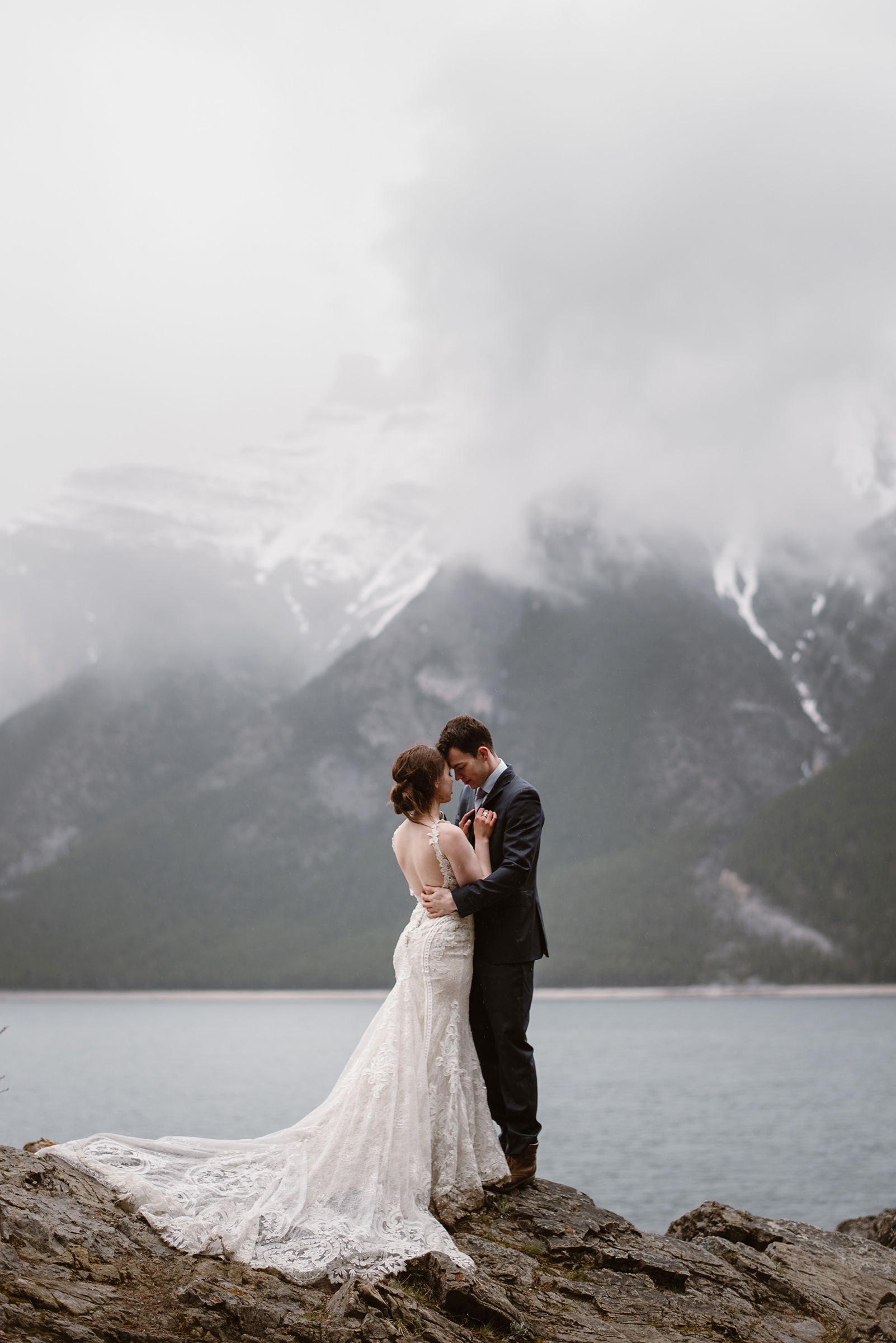 Face to face couple against water and misty mountains - photo by Virginia & Evan