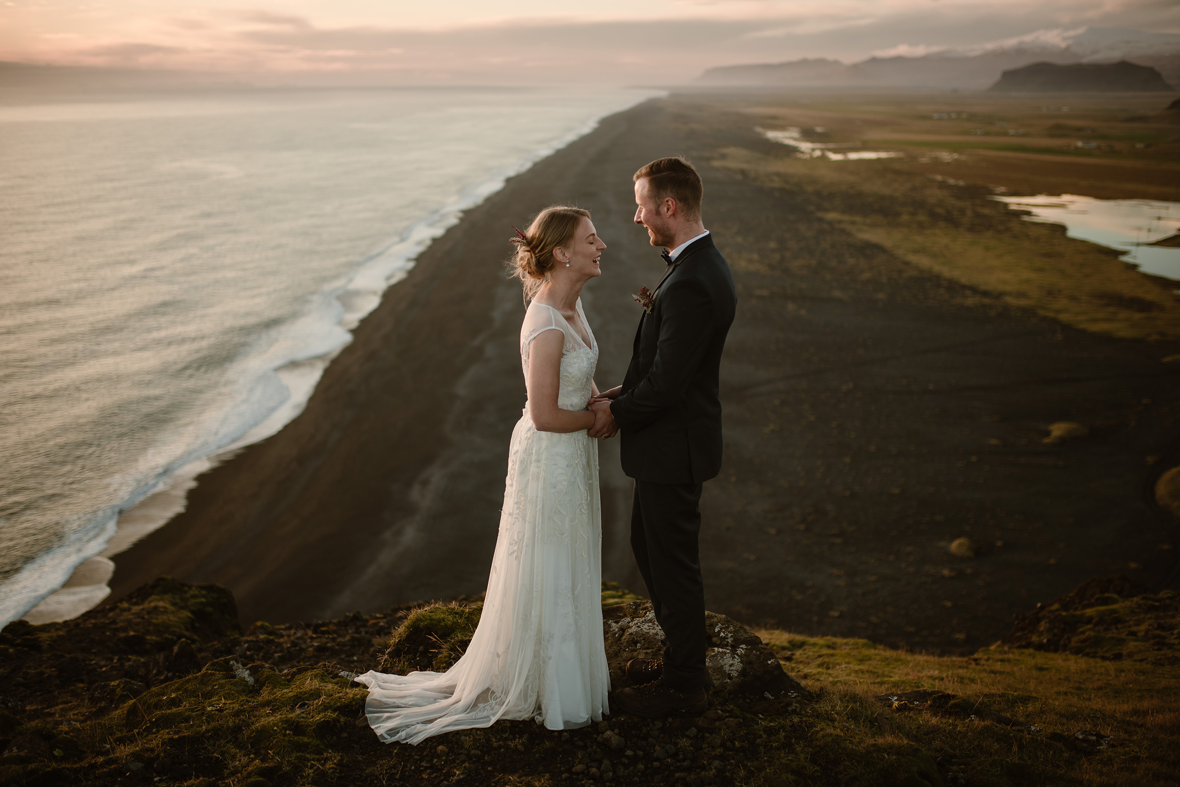 Face to face couple portrait on cliff above coastline - photo by Virginia & Evan