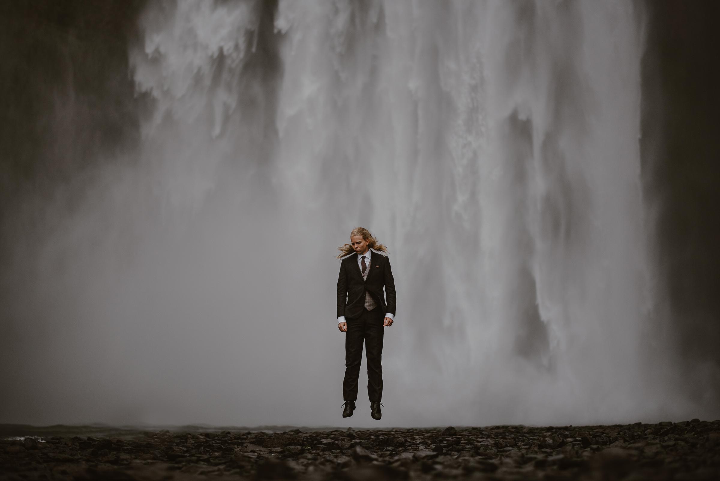 Groom levitating against waterfall - photo by Virginia & Evan