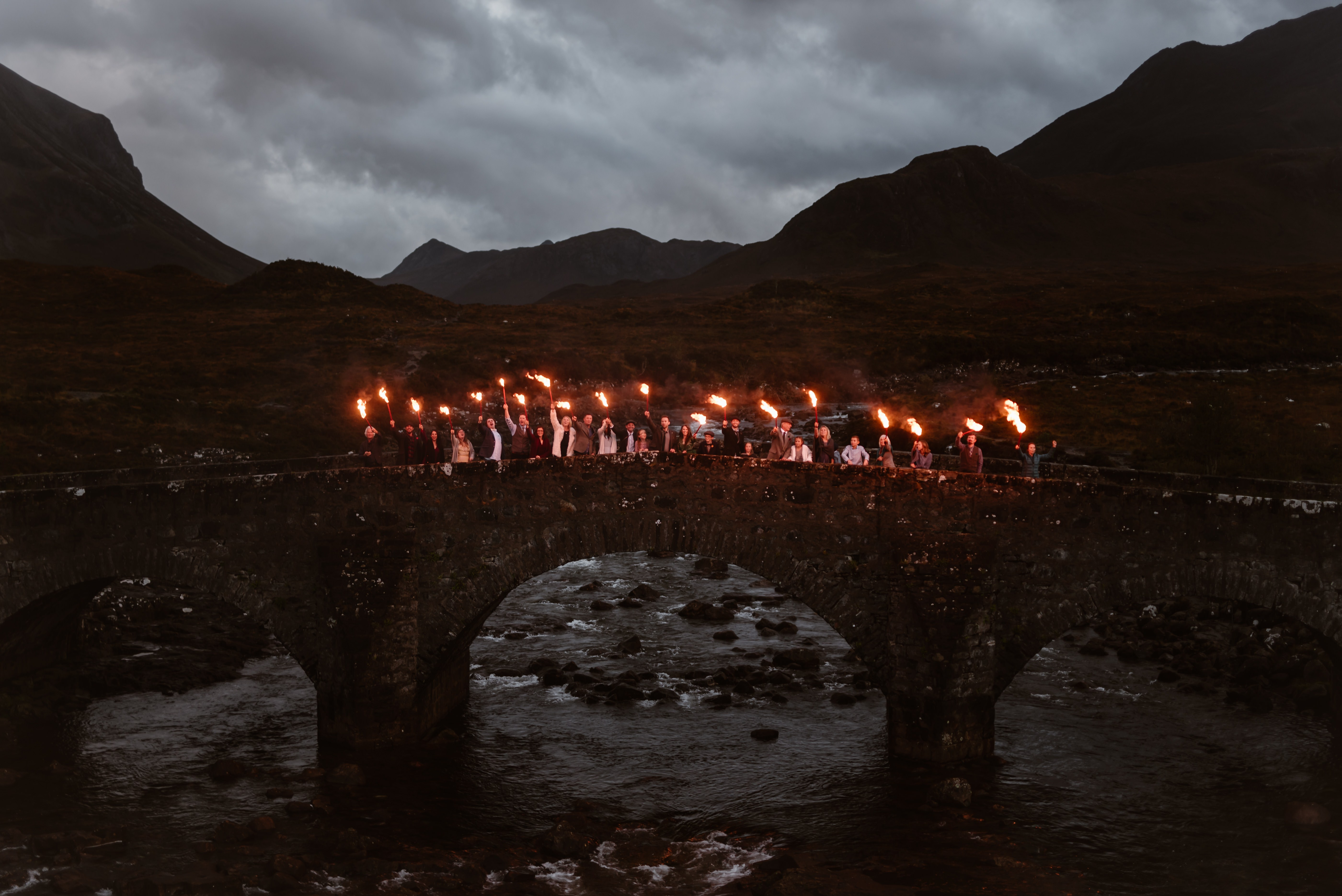 Bridal party with torches on bridge over river - photo by Virginia & Evan - Scotland