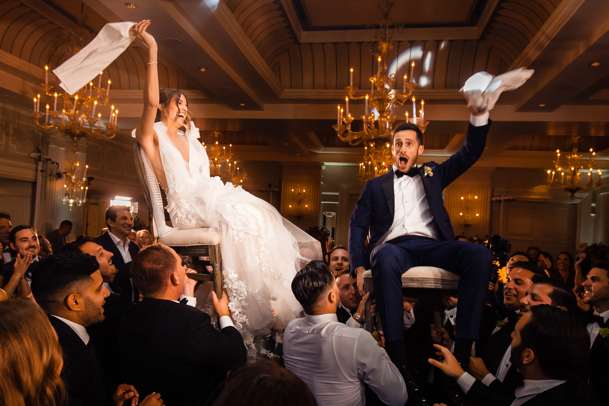 Bride and groom held aloft on chairs - photo by M. Hart - Los Angeles photographer