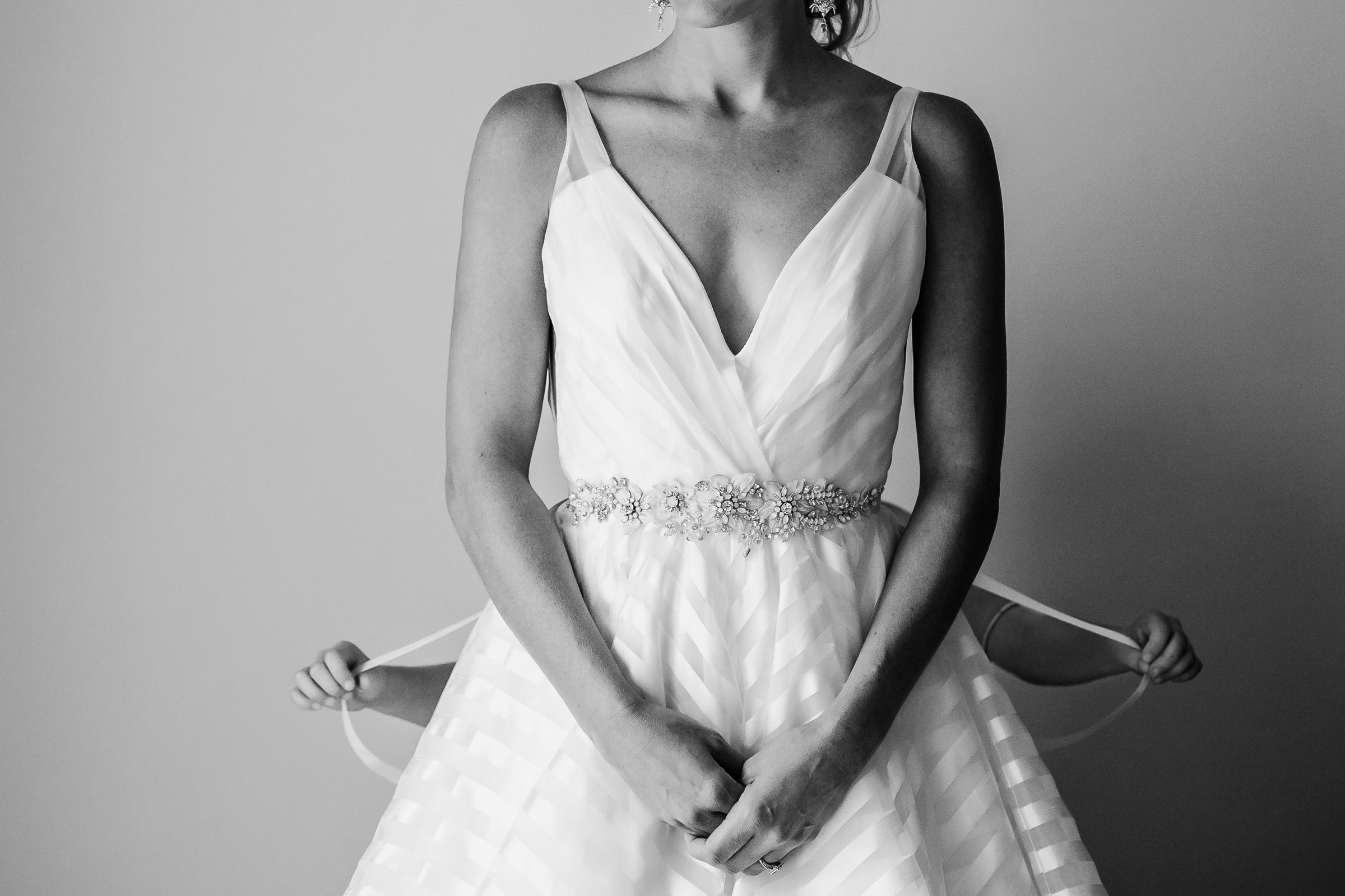 Bride in  having her dress laced up - photo by M. Hart - Los Angeles photographer