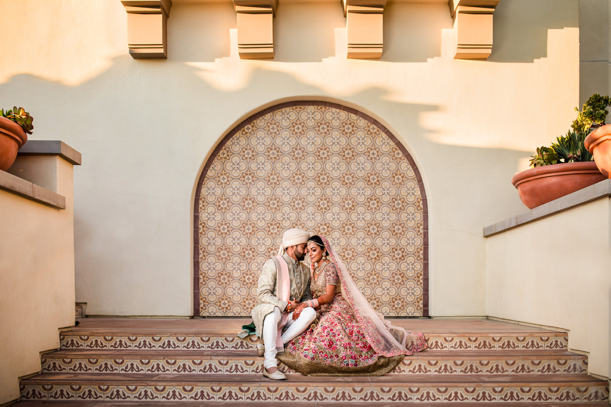 Indian couple in traditional attie on tiled stairway - photo by M.  Hart,  Los Angeles