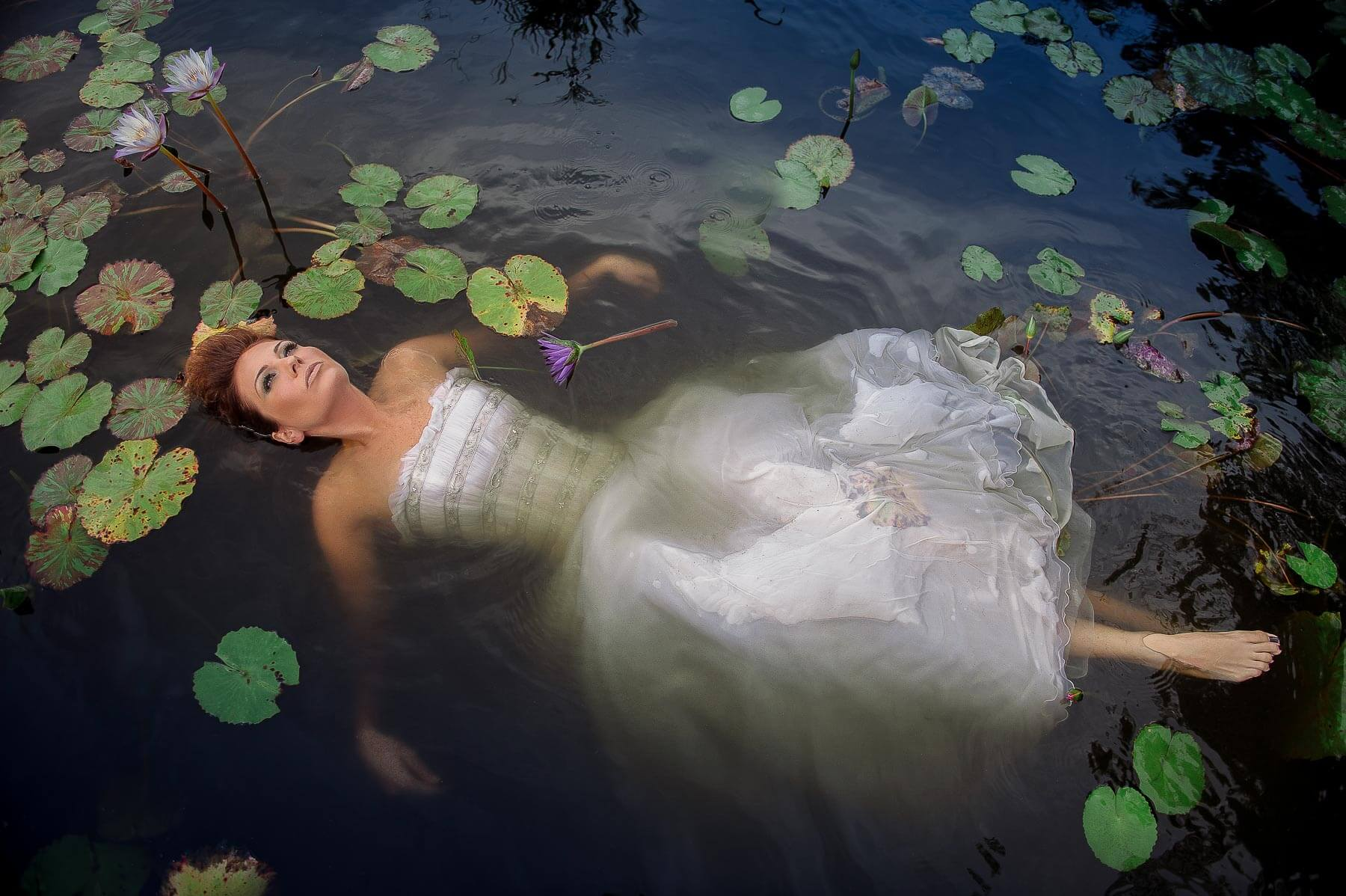 Bride floating in Bahamas lily pond - photo by Maloman Studios