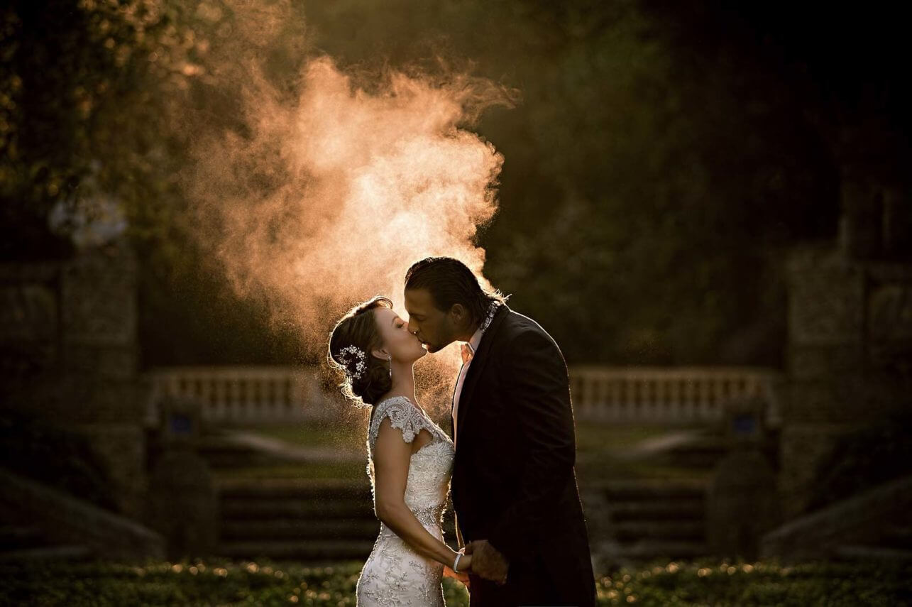 Couple kiss against bright smoke - photo by Maloman Studios