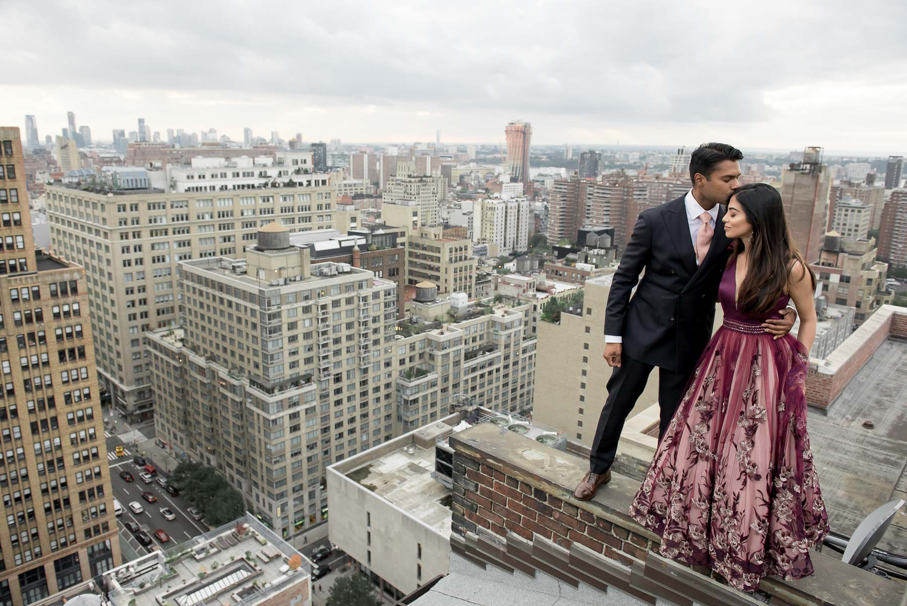 Couple on rooftop ledge against New York skyline - photo by Maloman Studios