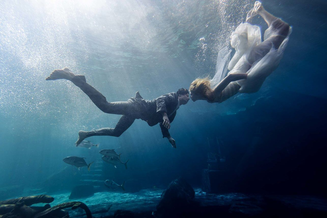 Couple underwater with fish - photo by Maloman Studios