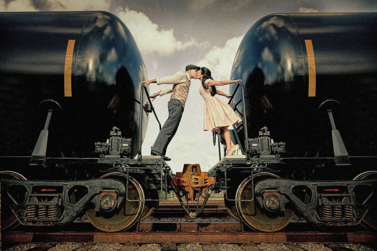 Engagement couple kissing between vintage train cars - photo by Maloman Studios