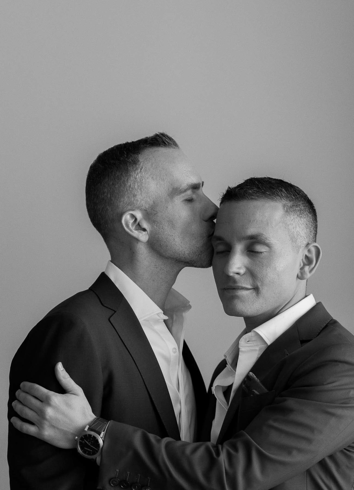 Eyes closed grooms kiss - photo by Maloman Studios