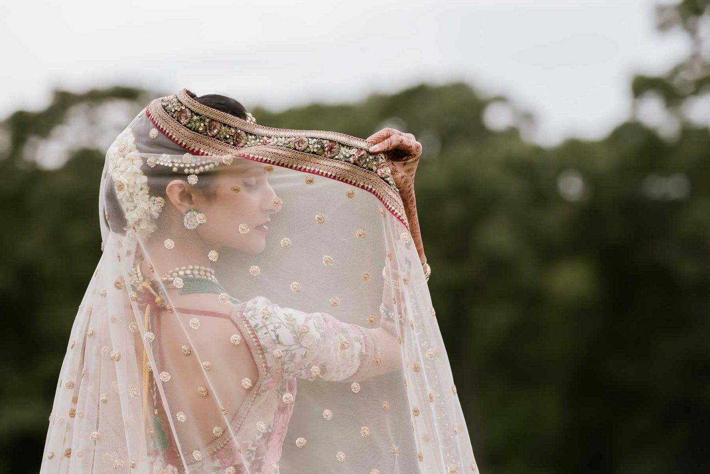 Indian bride seen through veil - photo by Maloman Studios