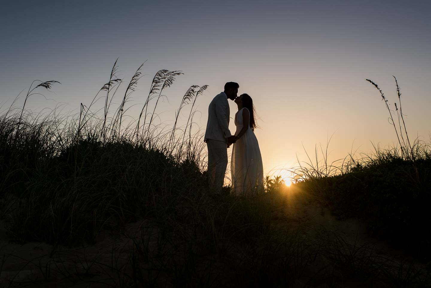 Silhouette couple in grasses at sunset - photo by Maloman Studios