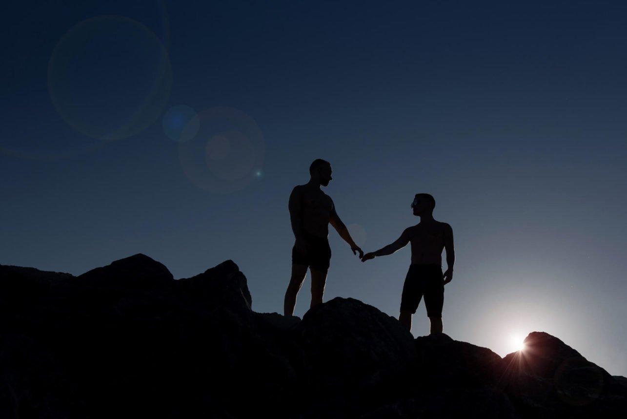 Silhouette engagement photo two men on ridge - photo by Maloman Studios