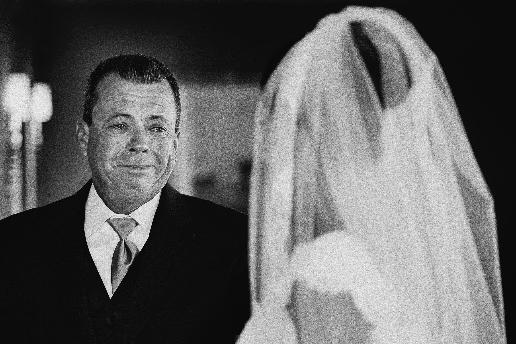 Teary eyed father looks at bride - photo by Maloman Studios