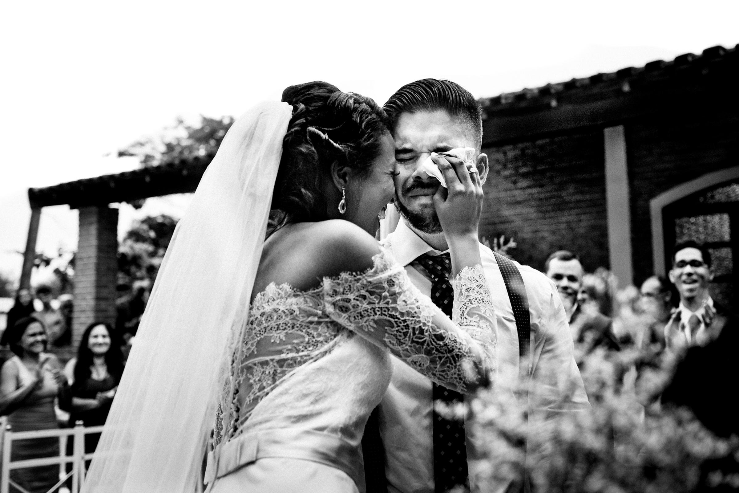 Bride wipes a tear for her groom - photo by Área da Fotografia