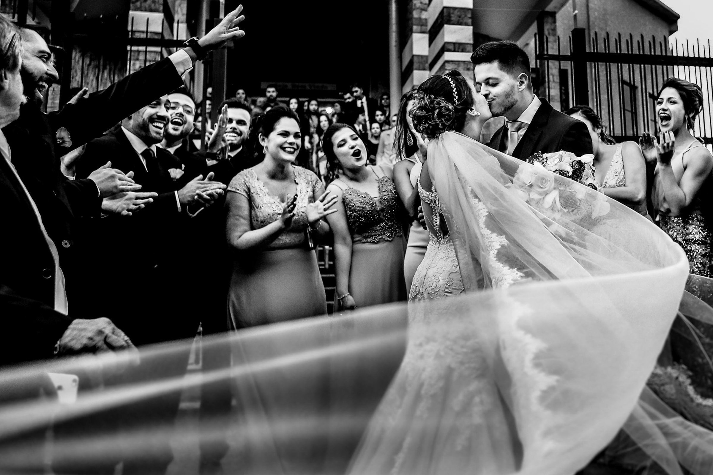 Guests cheer as couple kiss while veil blows in the wind - photo by Área da Fotografia - Portugal photographer