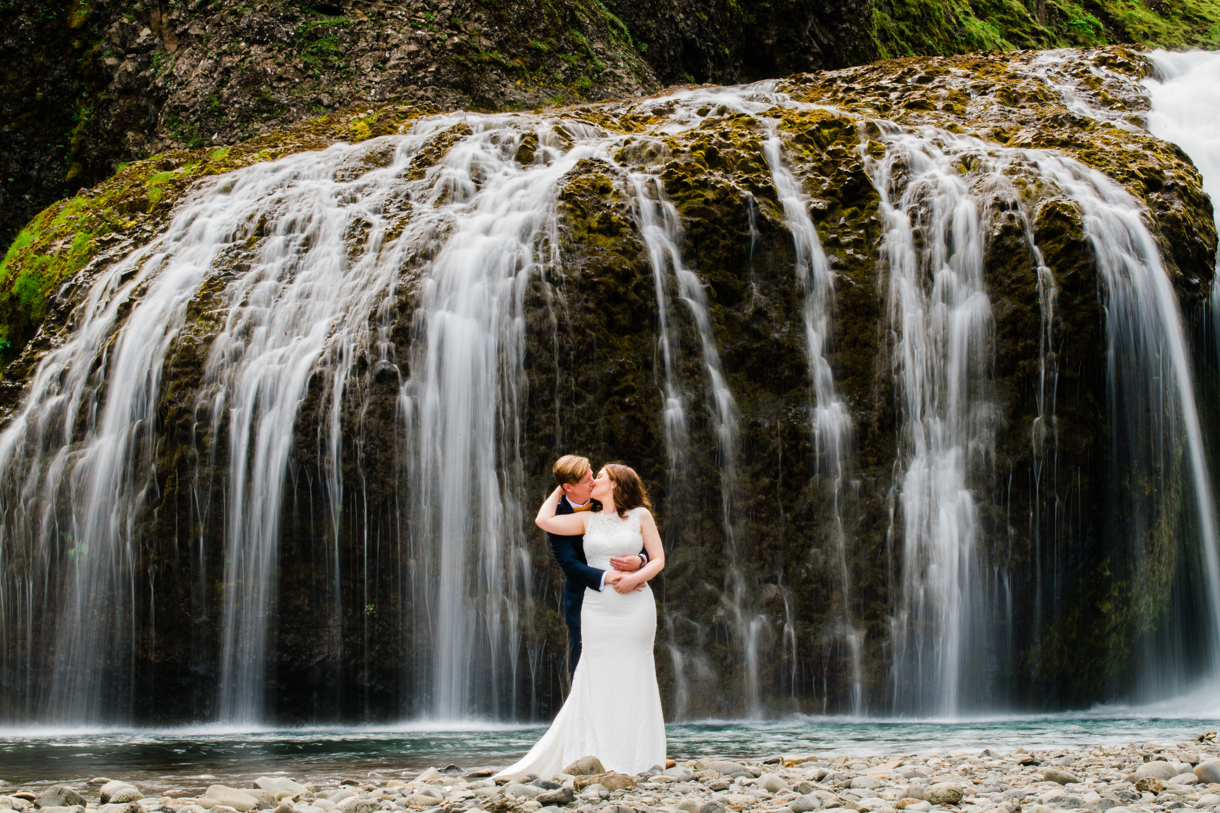 Couple embrace against waterfall in Iceland - photo by M&J Studios
