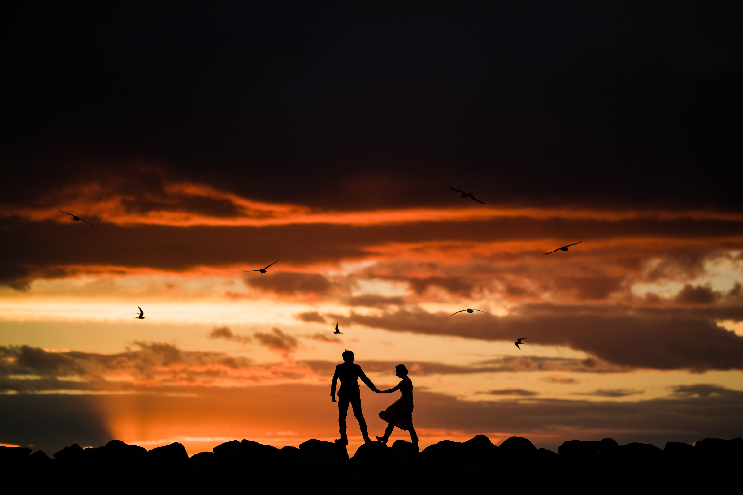 Couple silhouette on rocks at sunset in Iceland - photo by M&J Studios