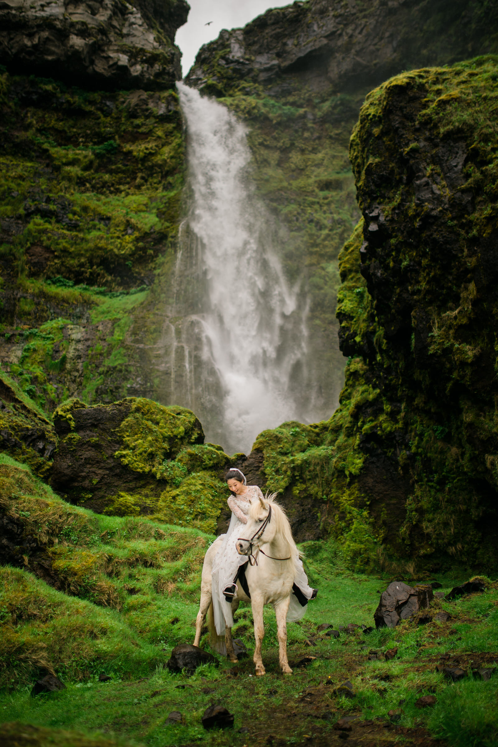 Elopement bride on white horse against Icelandic waterfall - photo by M&J Studios