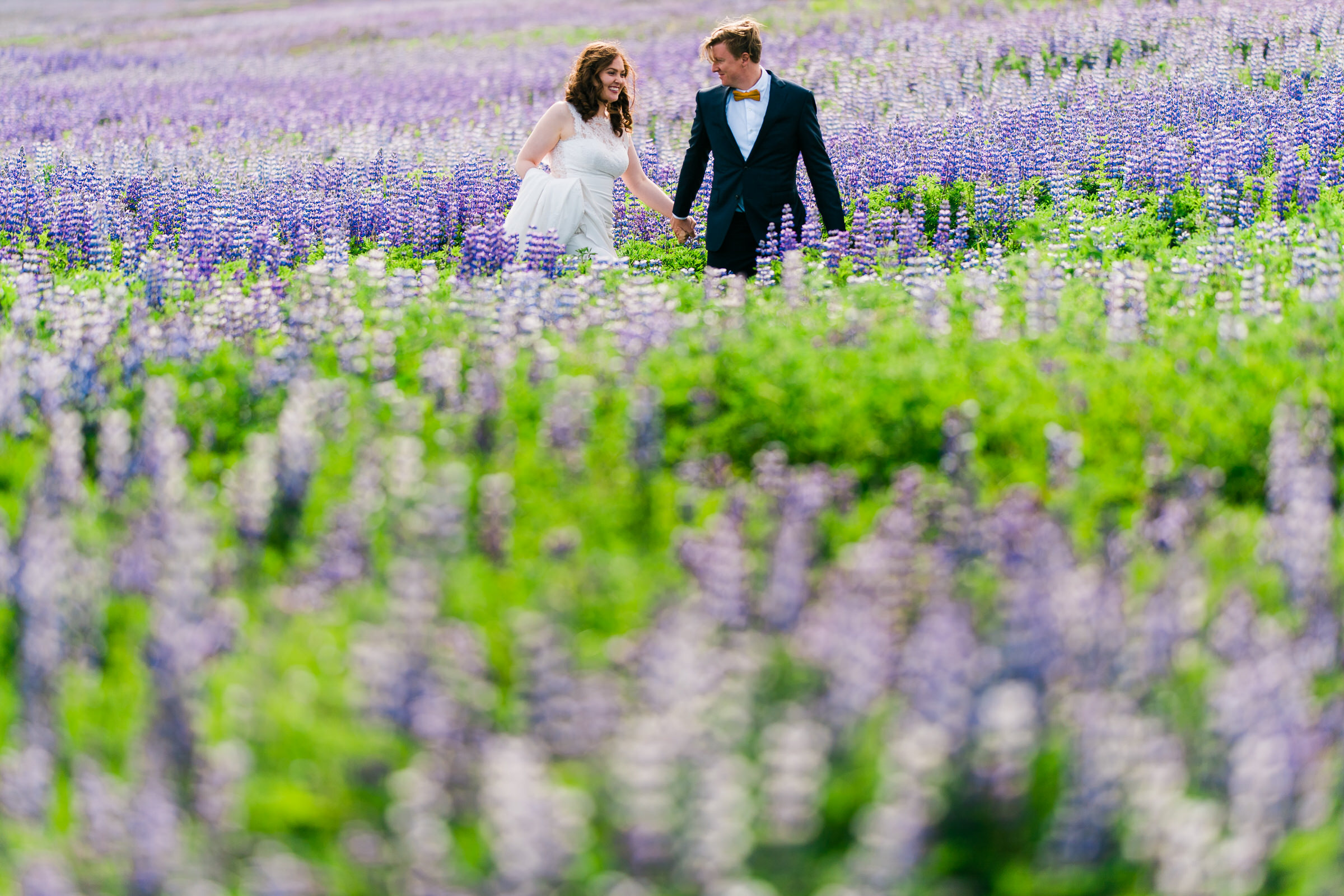 Elopement couple in field of flowers in Iceland - photo by M&J Studios