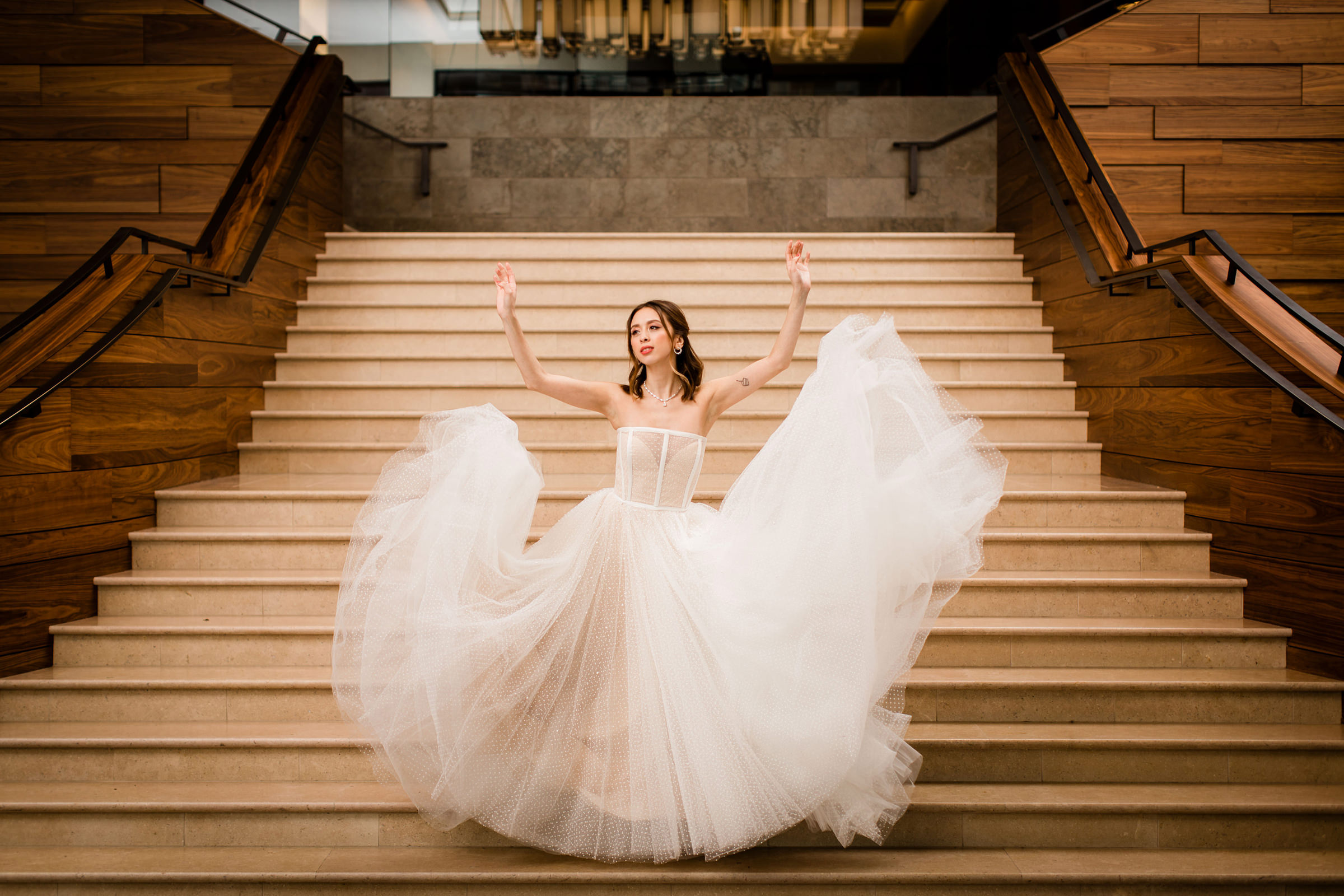 Arms in the air bride on staircase showing off gown - photo by Into Dust Photography