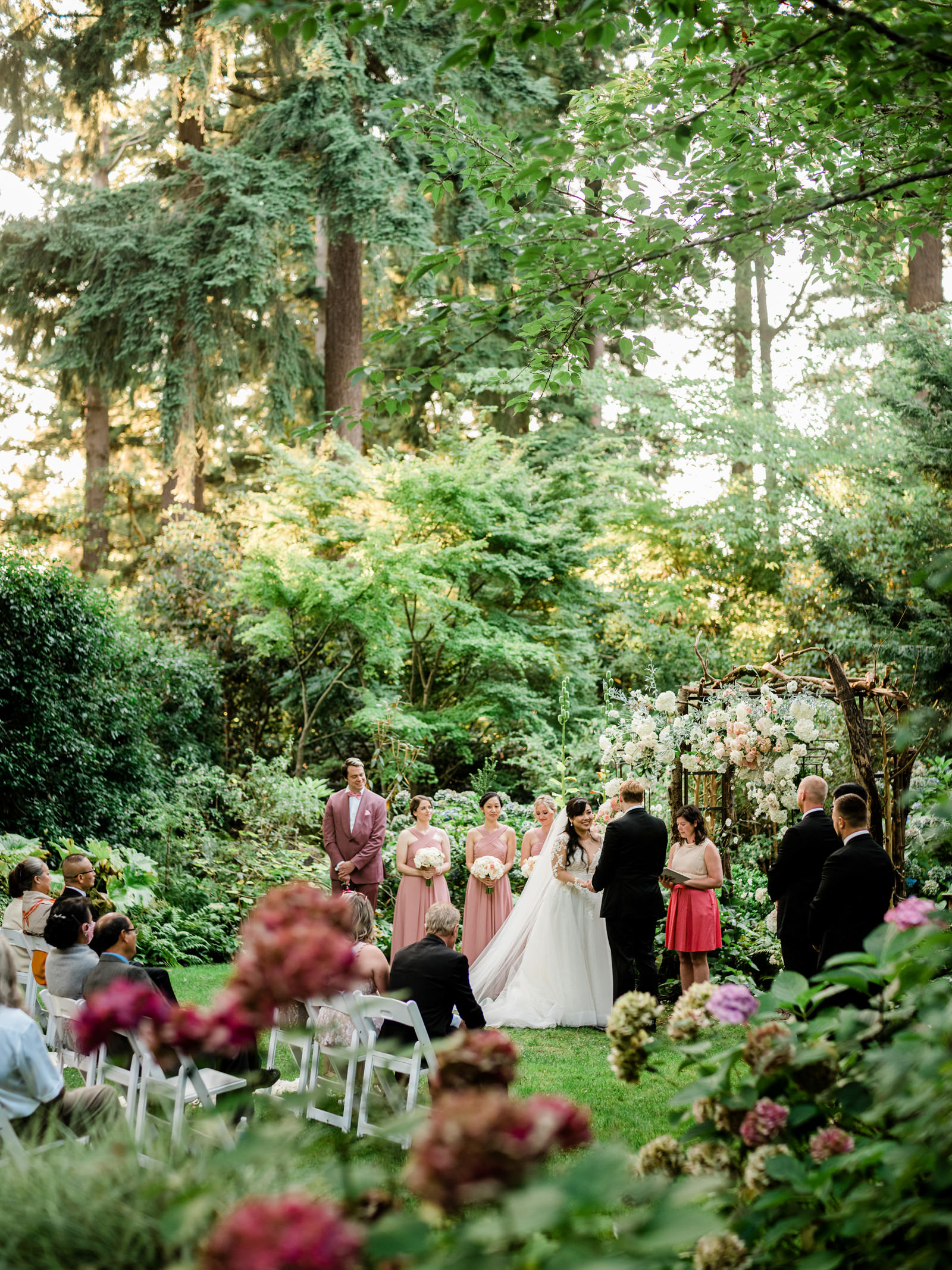 Ceremony in lush garden with bridal party - photo by Into Dust Photography