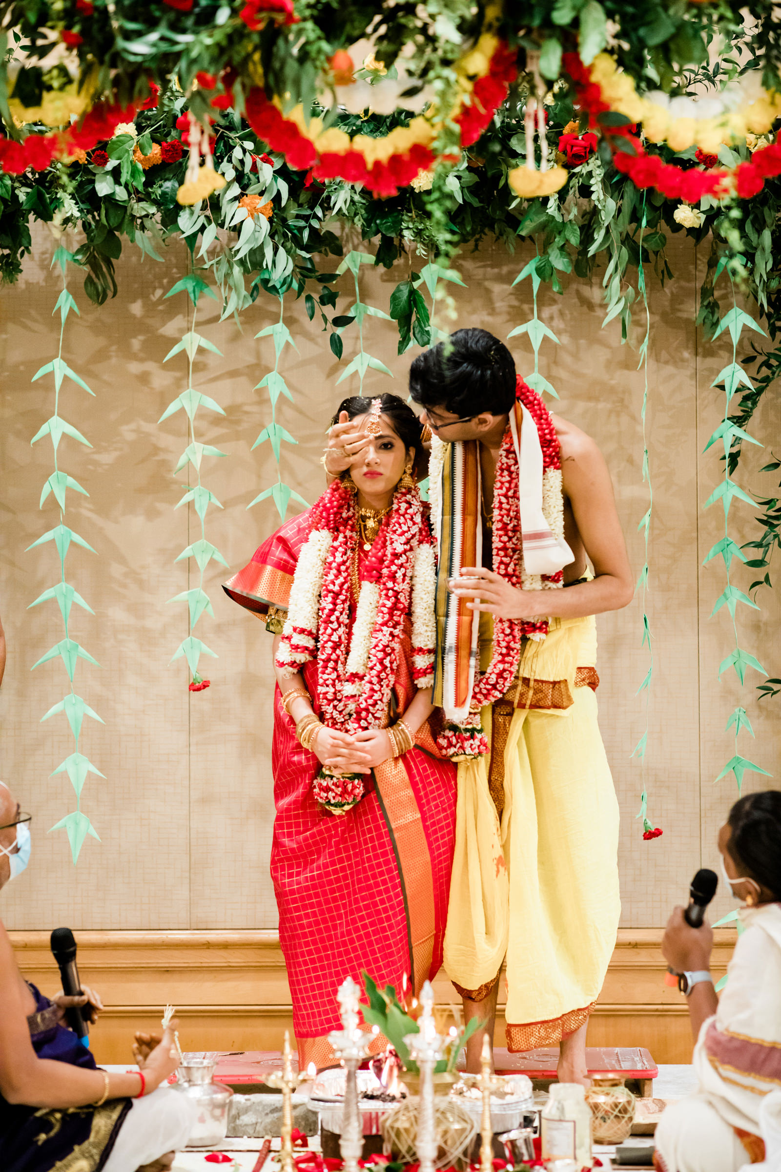 Groom covers bride eye at Indian ceremony - photo by Into Dust Photography