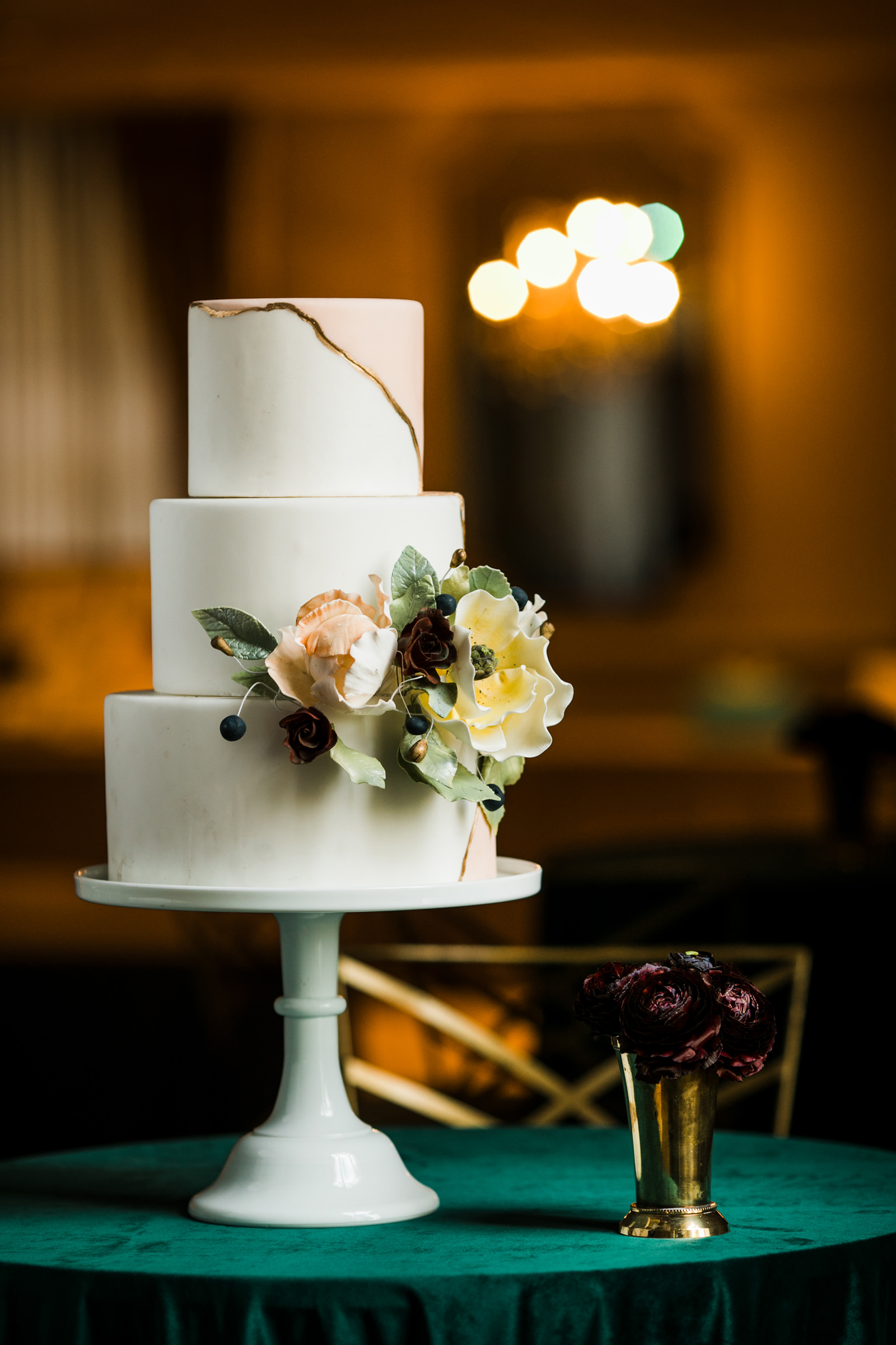 Portrait of elegant three tier wedding cake with flowers - photo by Into Dust Photography