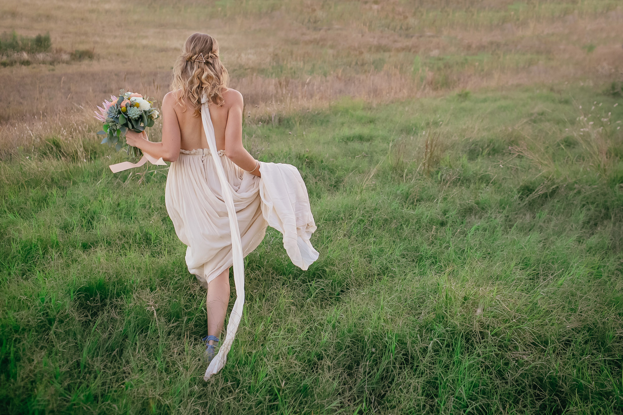 Bride walking in the grass - photo by Caroline's Collective