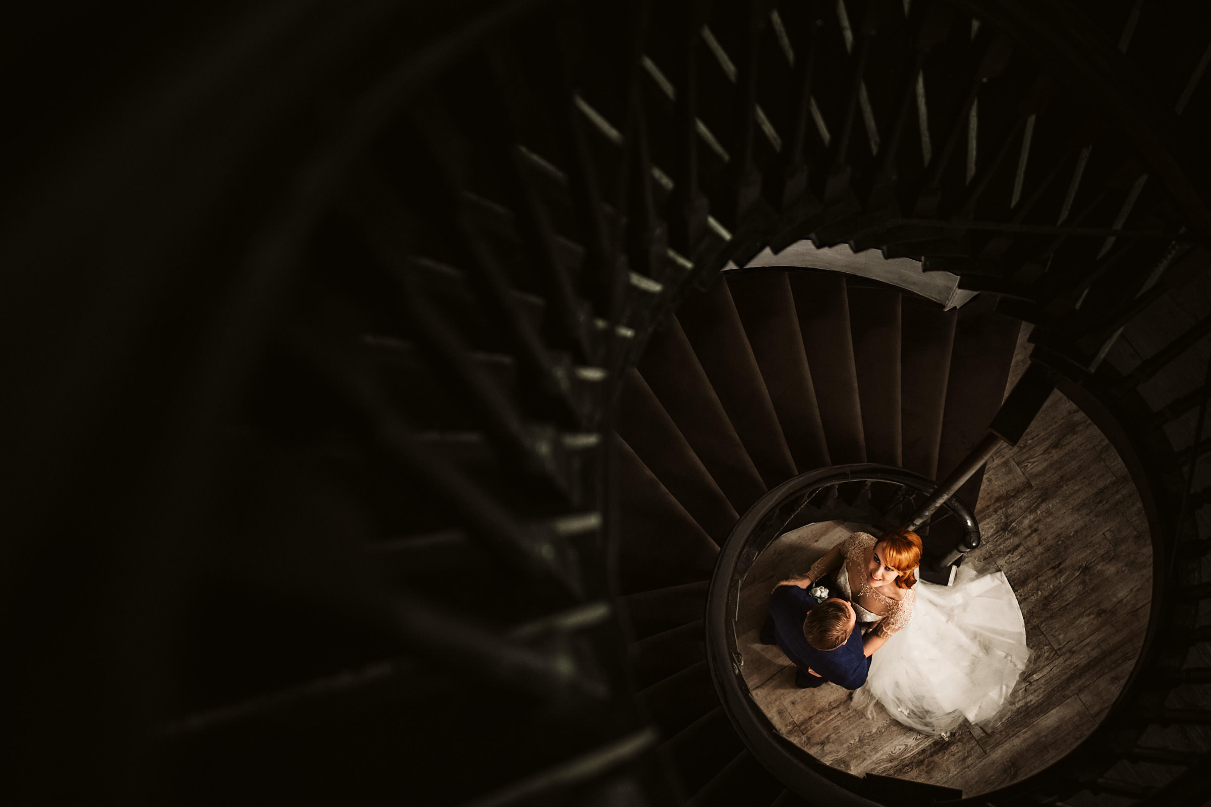 Bride looks up from spiral staircase landing - photo by Lima Conlon Photography