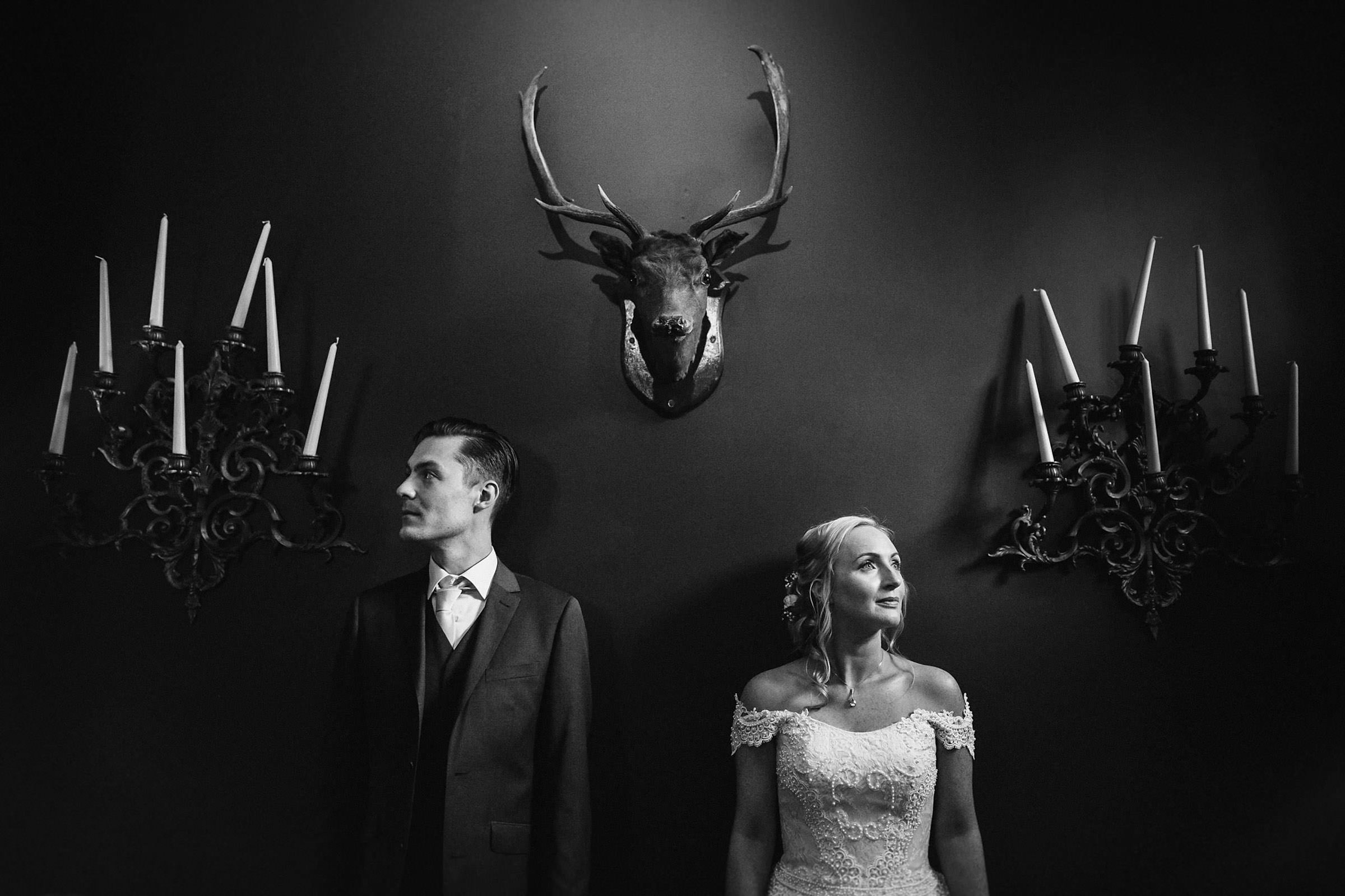 Couple portrait under taxidermy and sconces - photo by Lima Conlon Photography