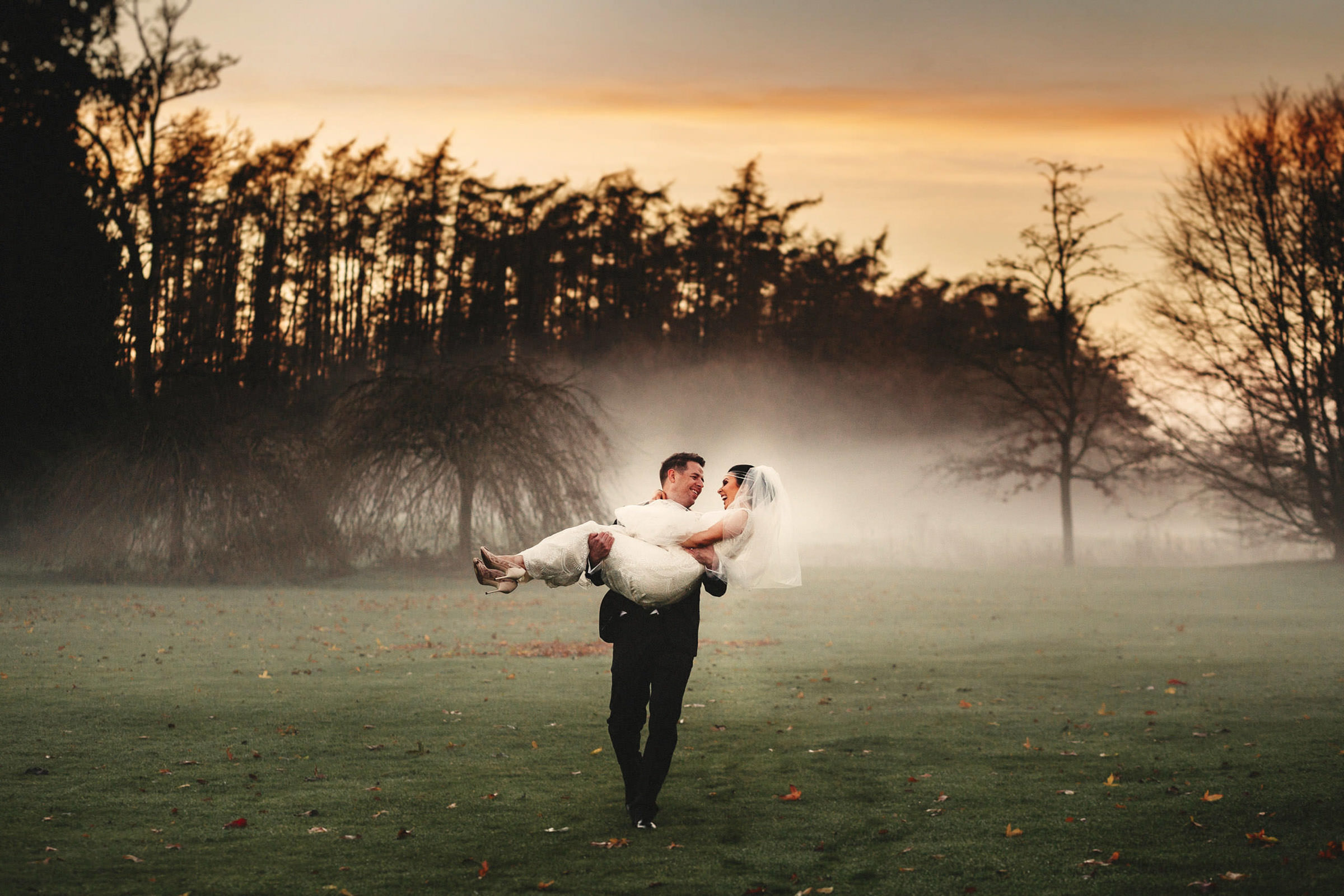 Groom carries bride on misty Ireland field - photo by Lima Conlon Photography