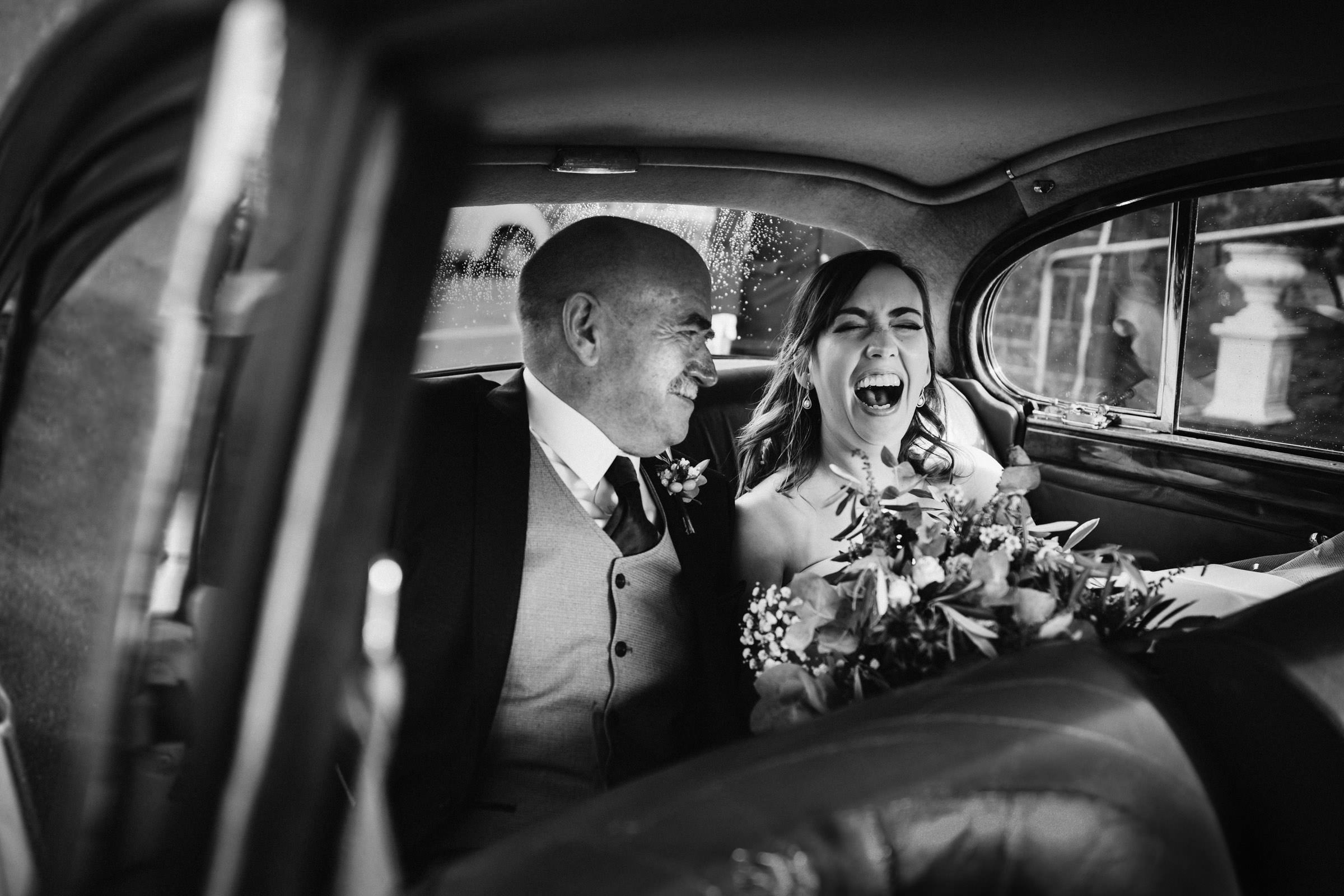 Laughing bride in car with father - photo by Lima Conlon Photography