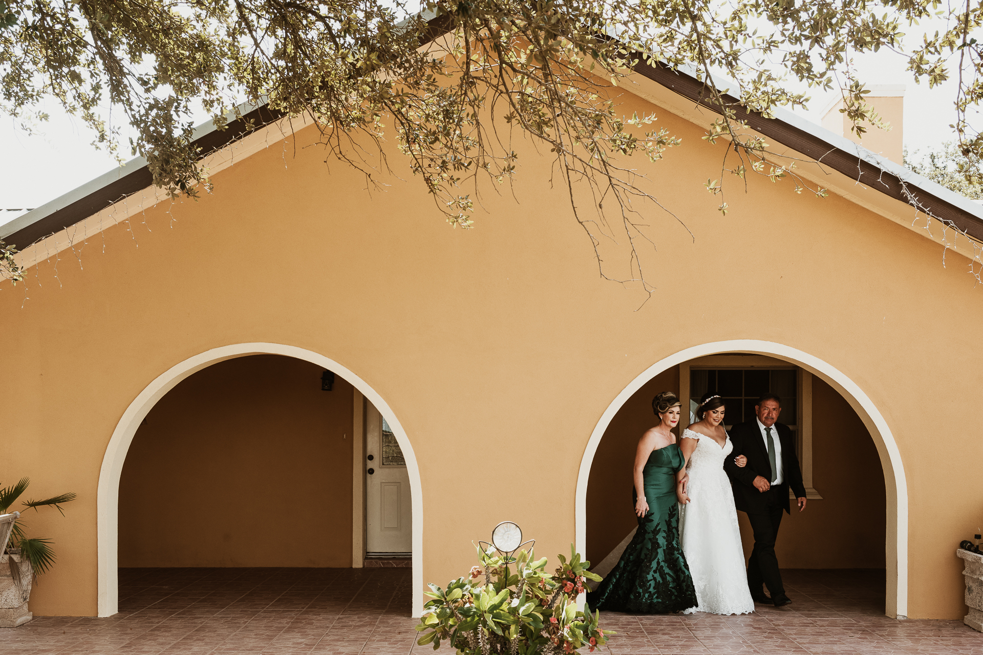 Bride and parents under architectural arch- photo by Philip Thomas Photography