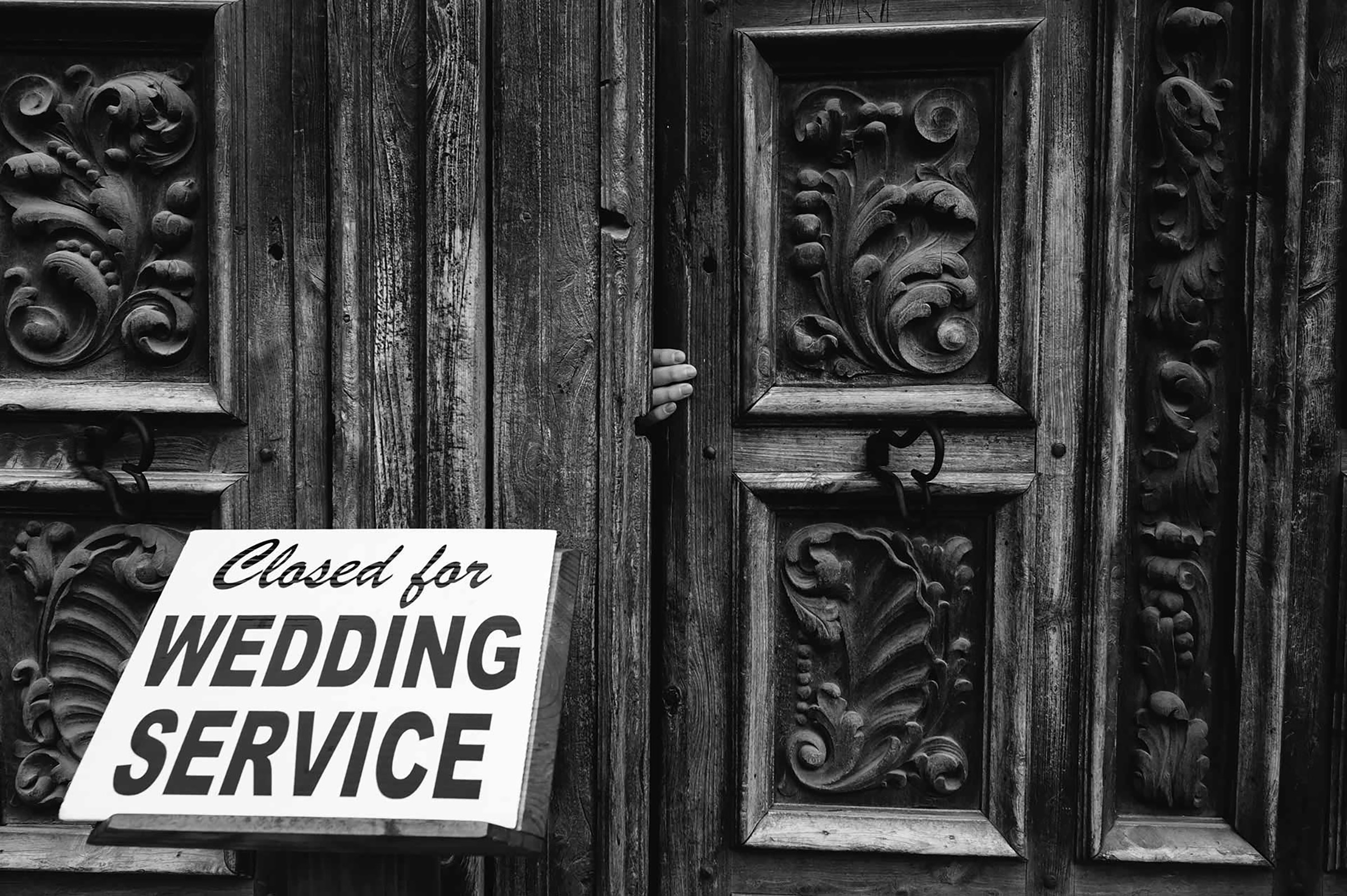 Hand in door with Closed for Wedding Service sign - photo by Philip Thomas Photography