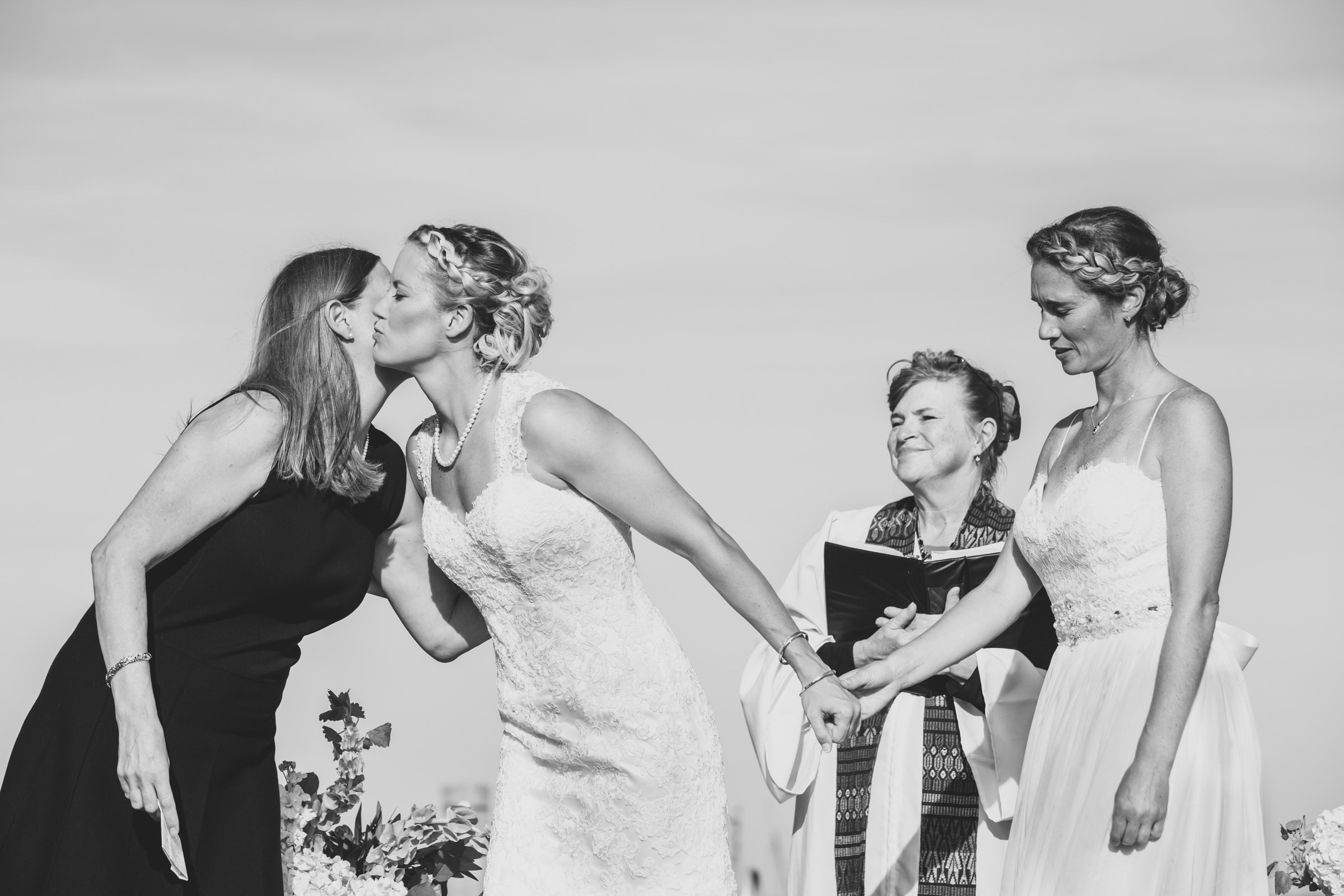 Bride turns to kiss mom at ceremony - photo by Katie Kaizer Photography