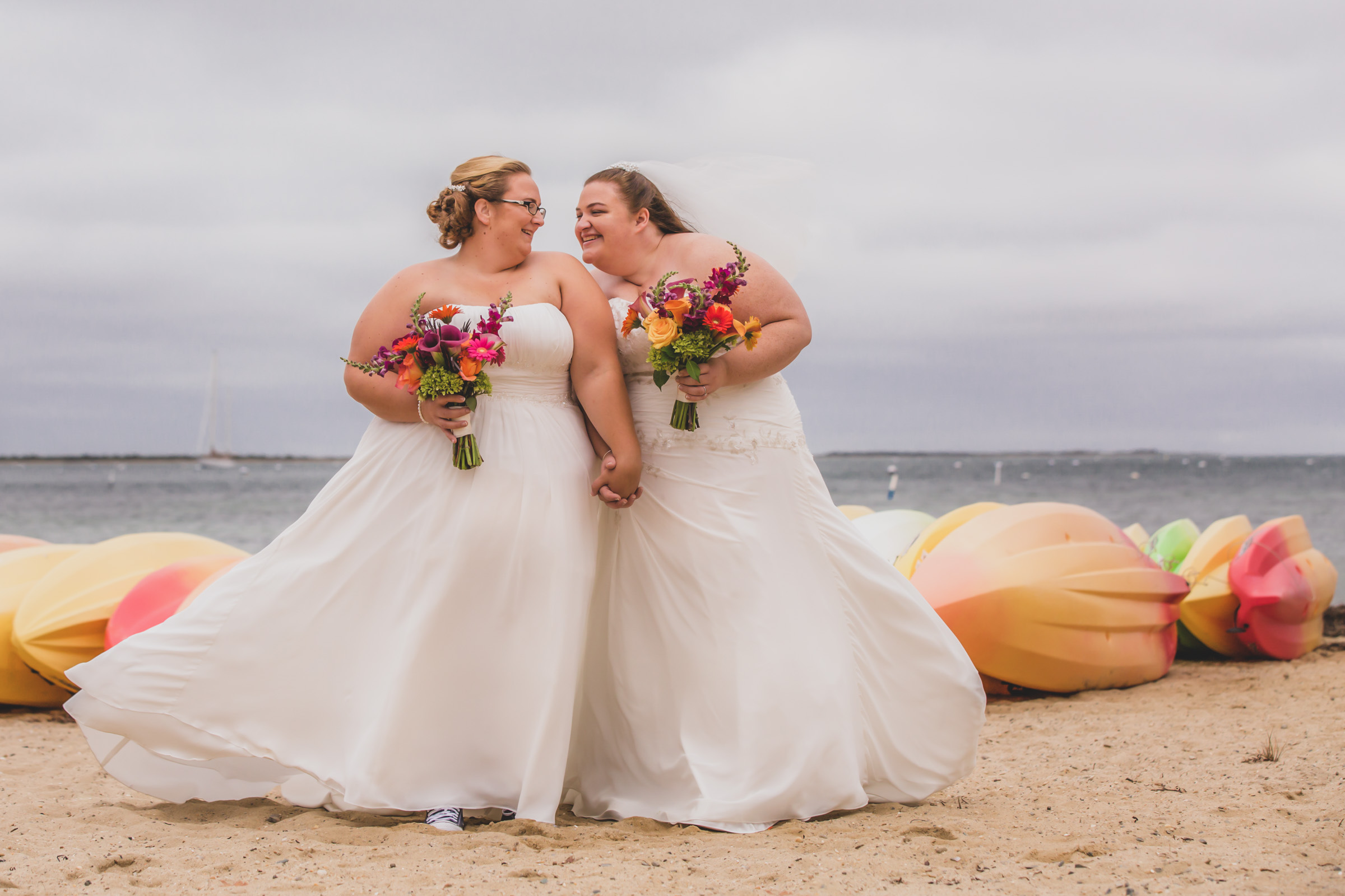 Brides on beach with bright bouquets - photo by Katie Kaizer Photography
