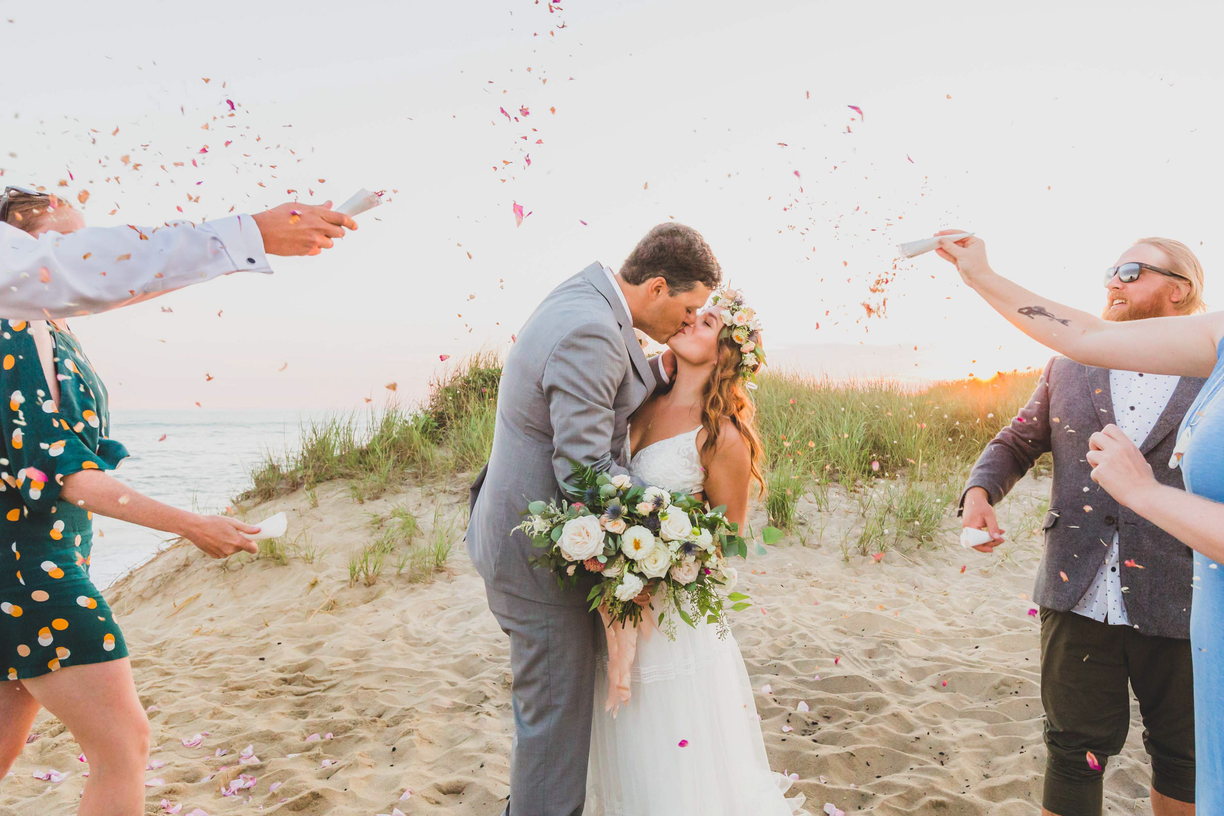 Ceremonial couple kiss under confetti - photo by Katie Kaizer Photography