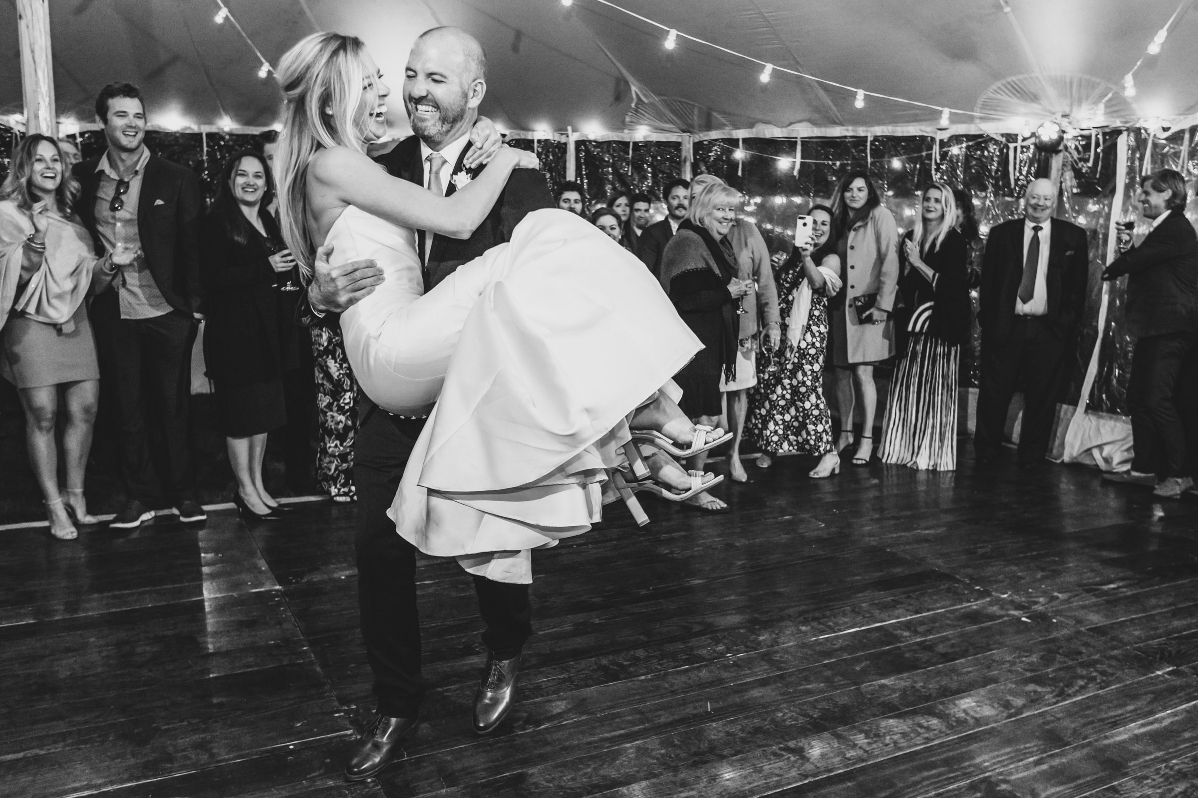 Groom lifts bride at dance party - photo by Katie Kaizer Photography