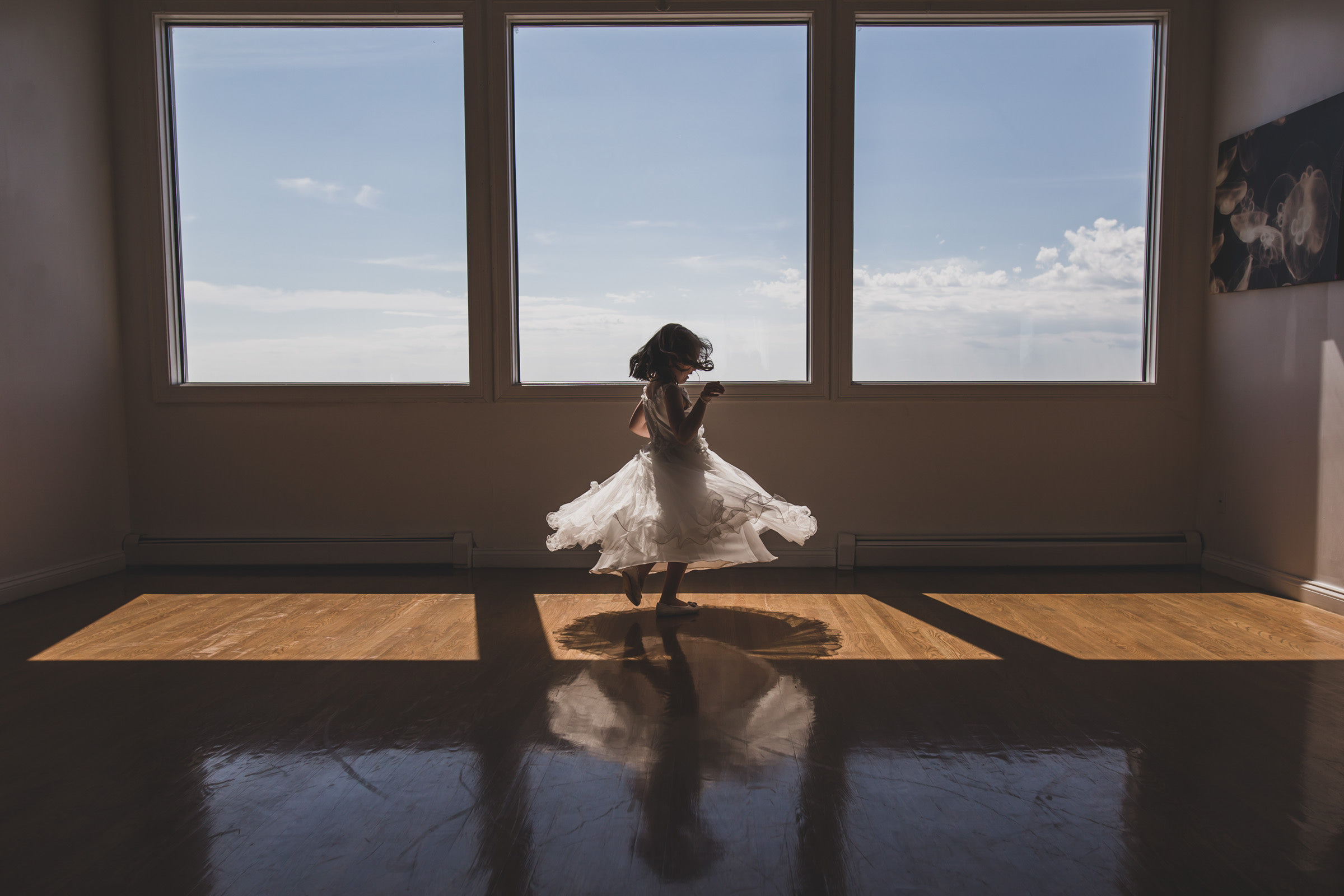 Little girl dancing by triple windows - photo by Katie Kaizer Photography