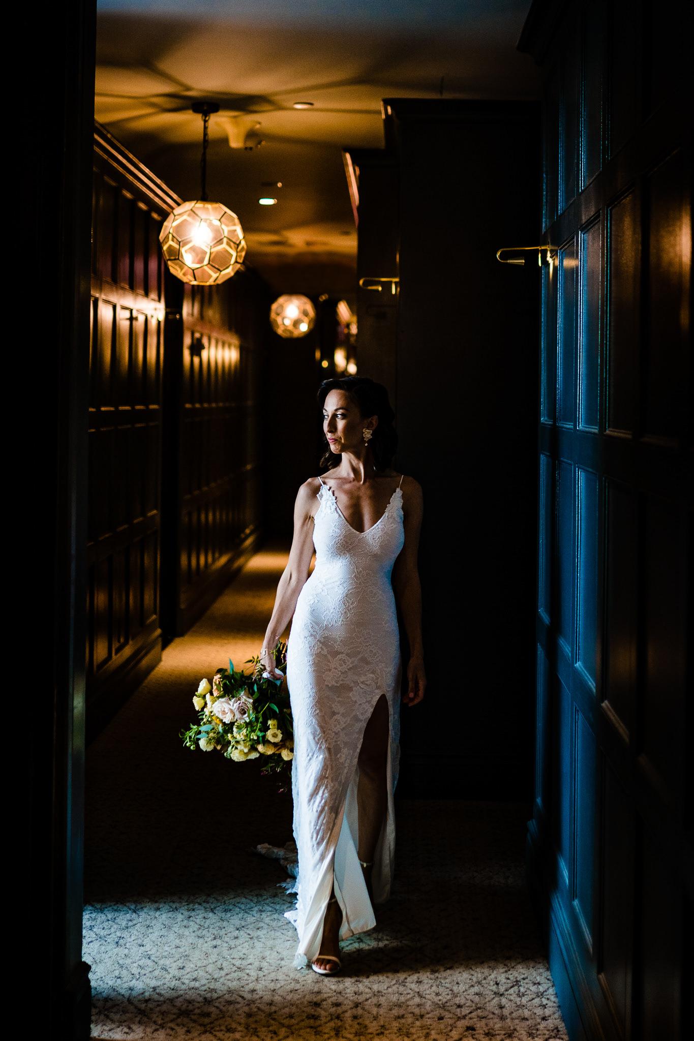 Bride interior portrait in dark hallway - photo by John Winter Photography