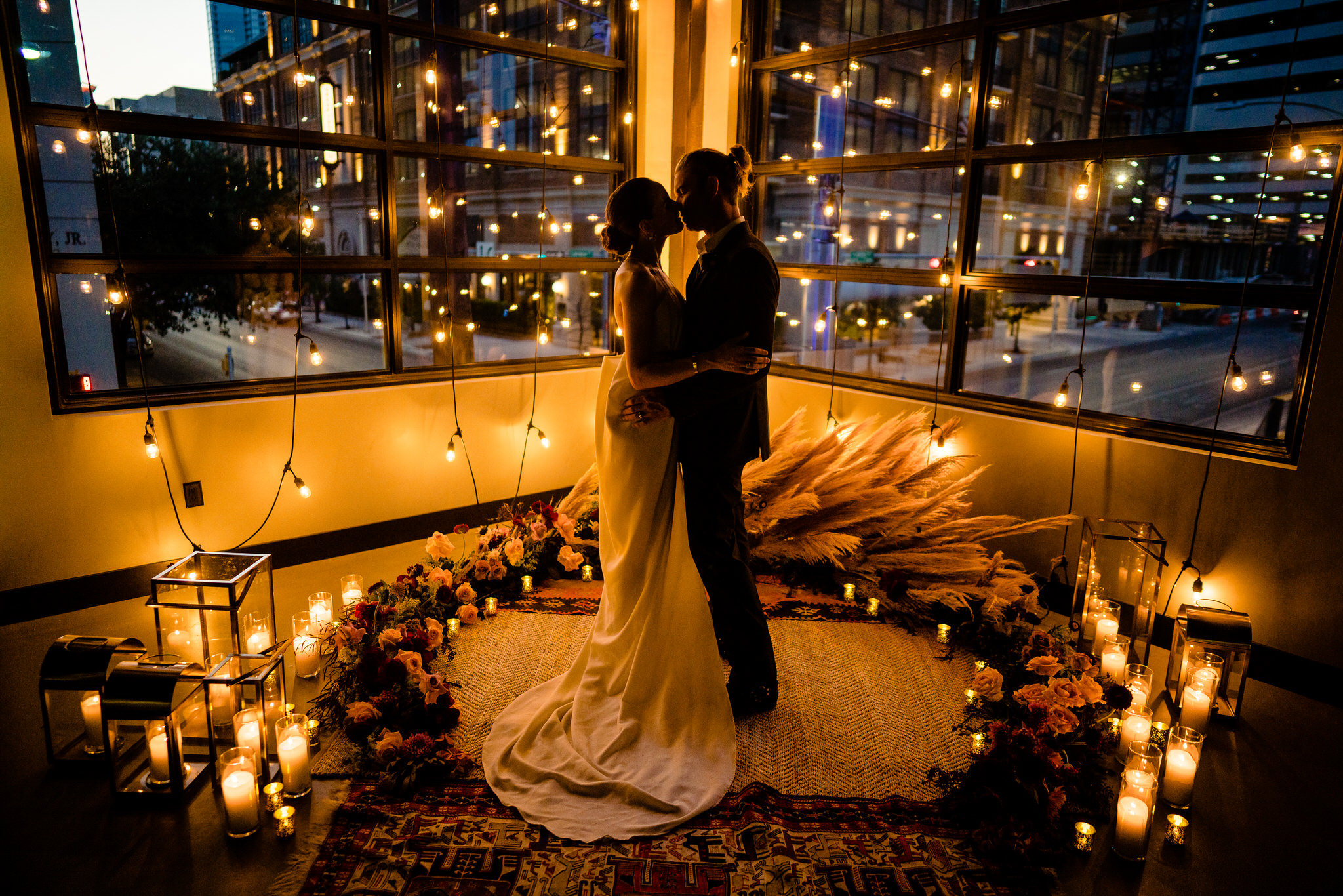 Evening couple portrait amid flowers, candles and urban view - photo by John Winters Photography